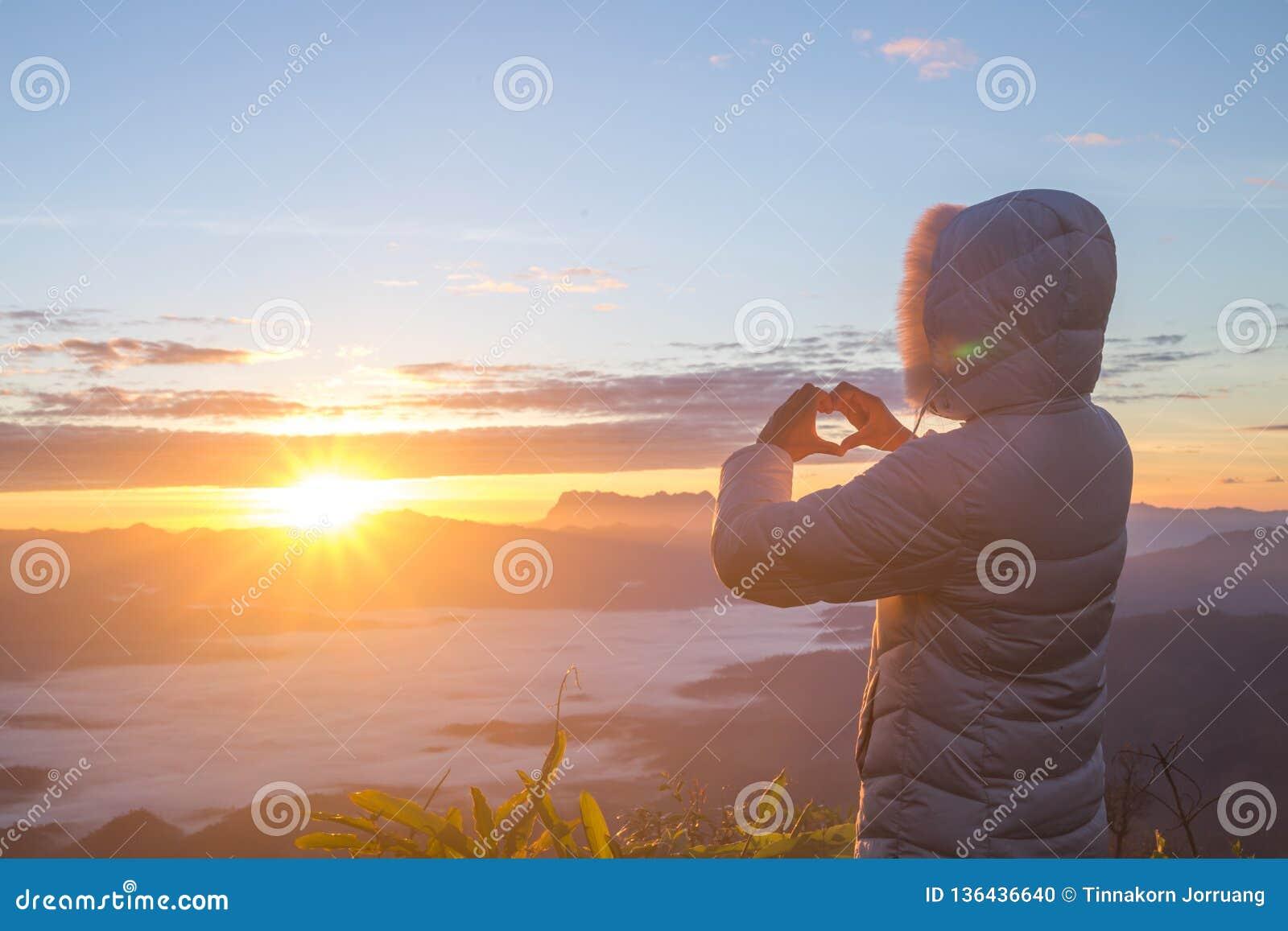 A mulher que faz a forma do coração durante a elevação do sol, deus é conceito do amor, forma do coração, turismo da montanha, sí