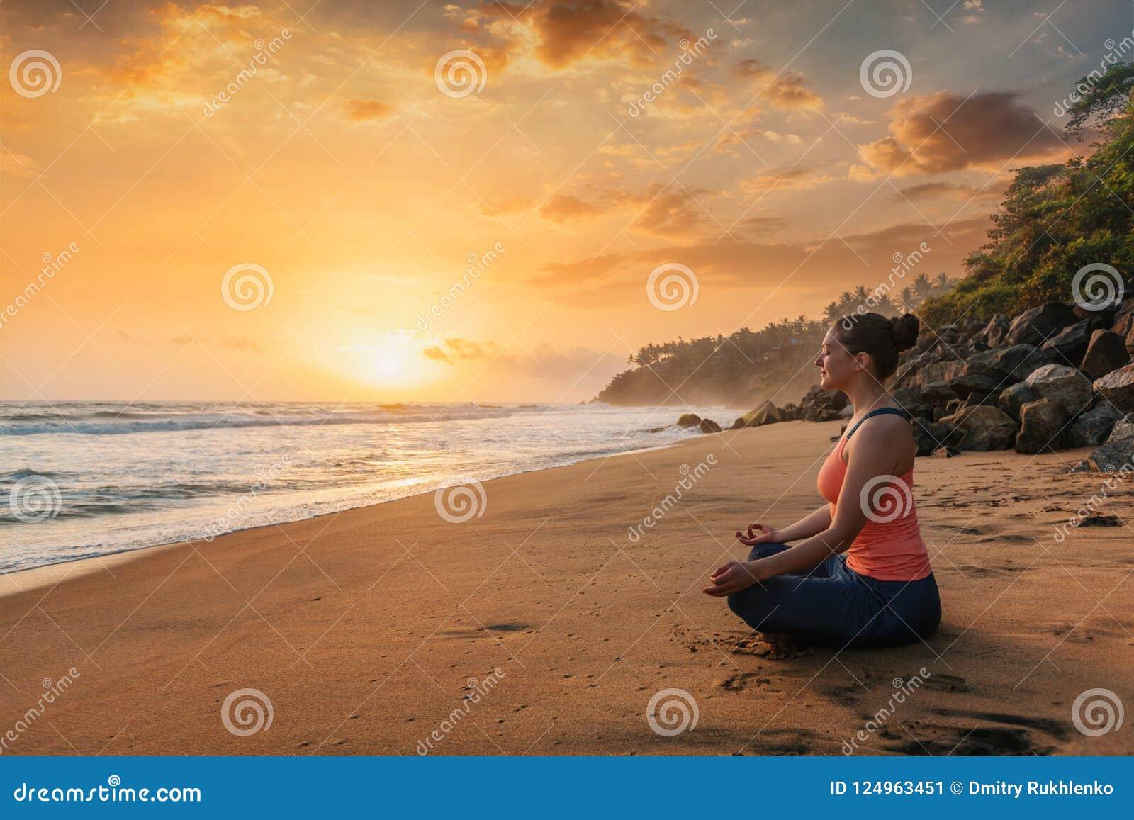 Mulher que faz a ioga na praia - pose dos lótus de Padmasana