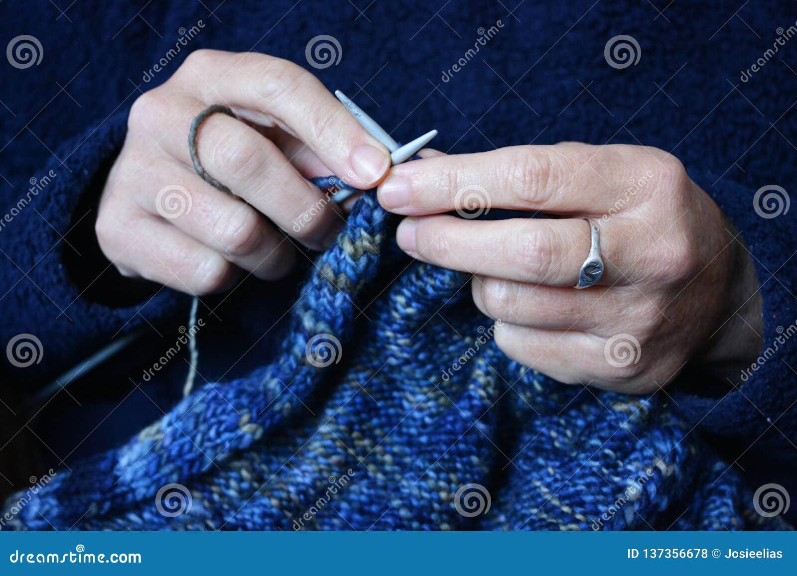 Mulher que faz malha uma camiseta de lã, foco em agulhas