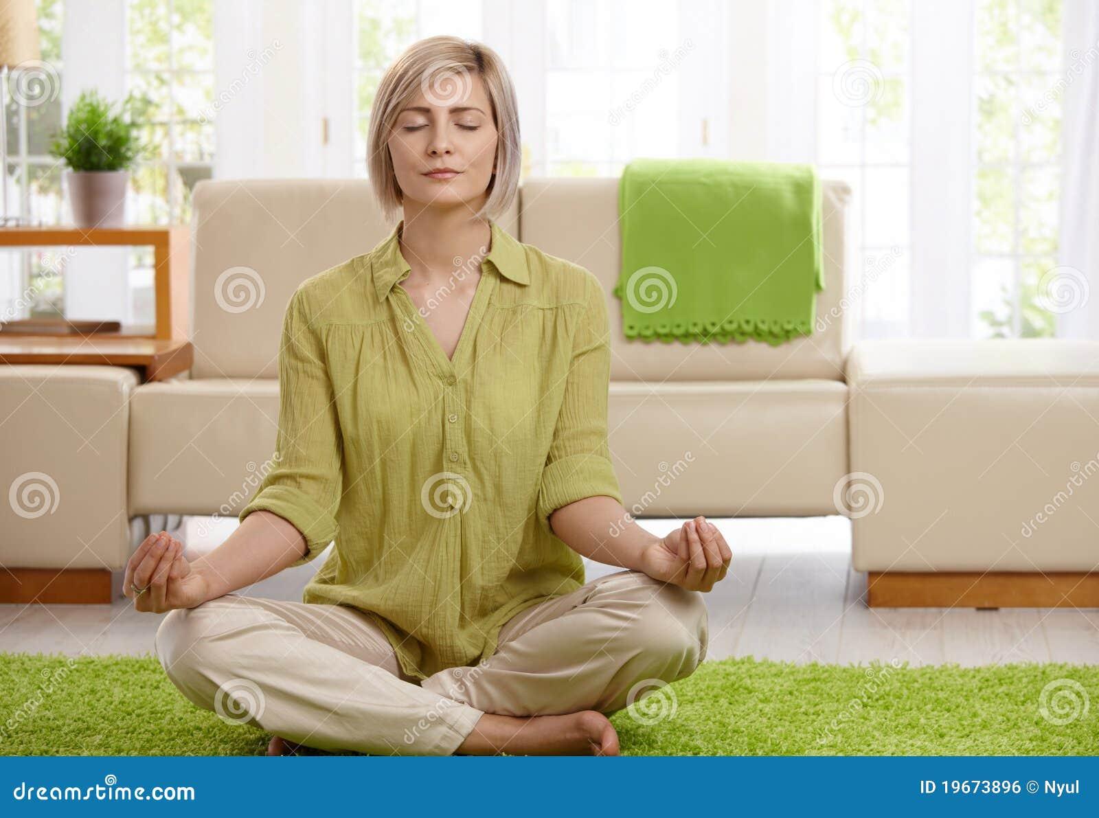 Mulher que faz a meditação da ioga em casa