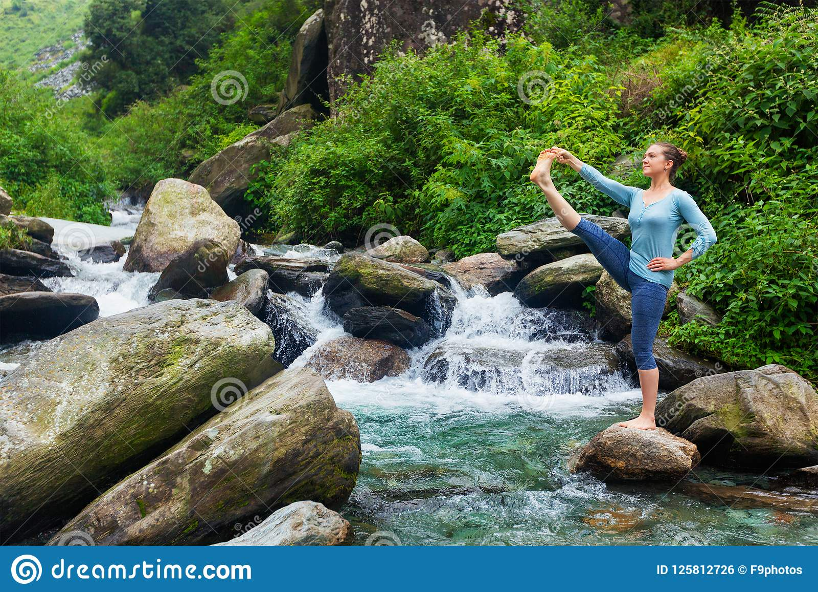 Mulher que faz o asana da ioga de Ashtanga Vinyasa fora na cachoeira
