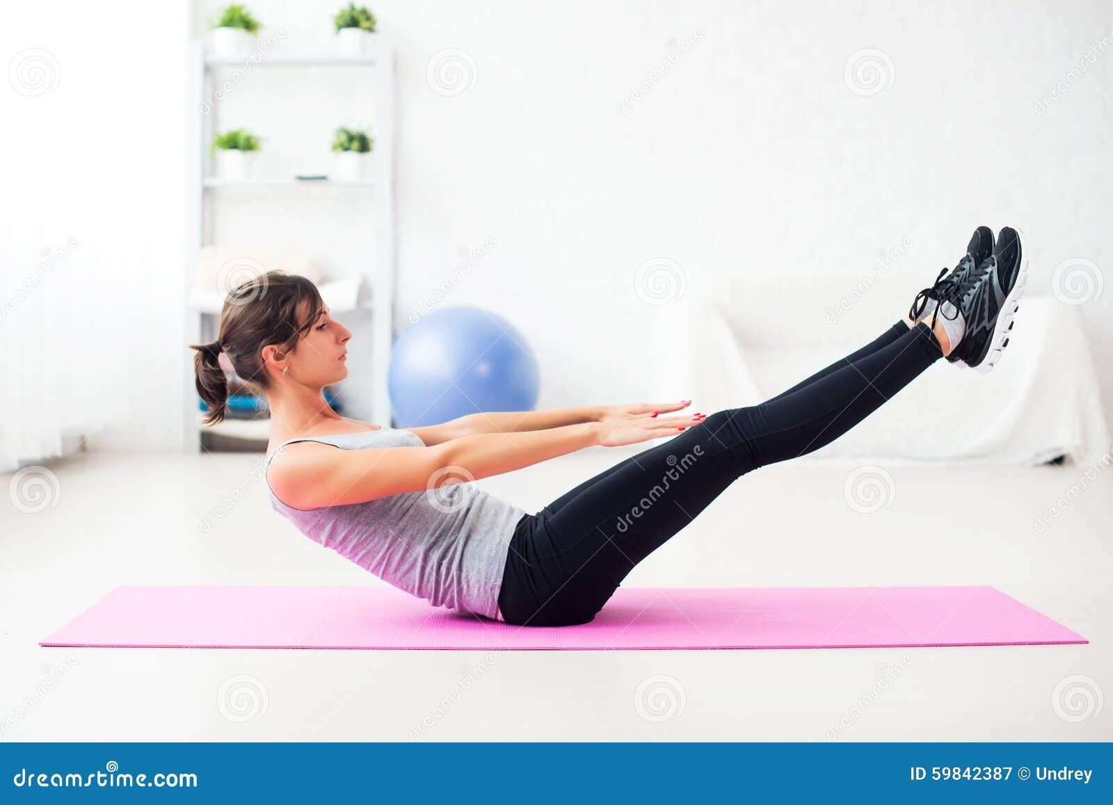 Mulher que faz o exercício abdominal na esteira em casa