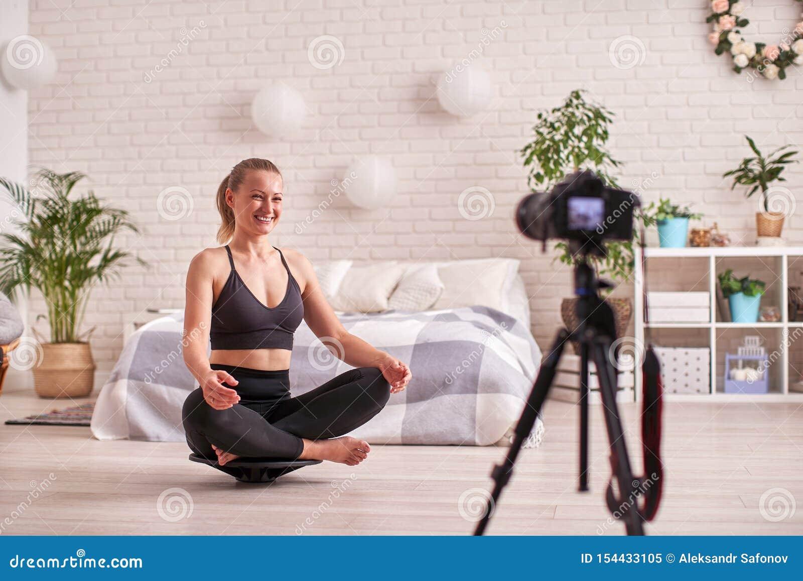 Mulher que faz o exercício em um equilibrador especial do simulador o sportswear atlético louro, casa exercitou reforça os múscul
