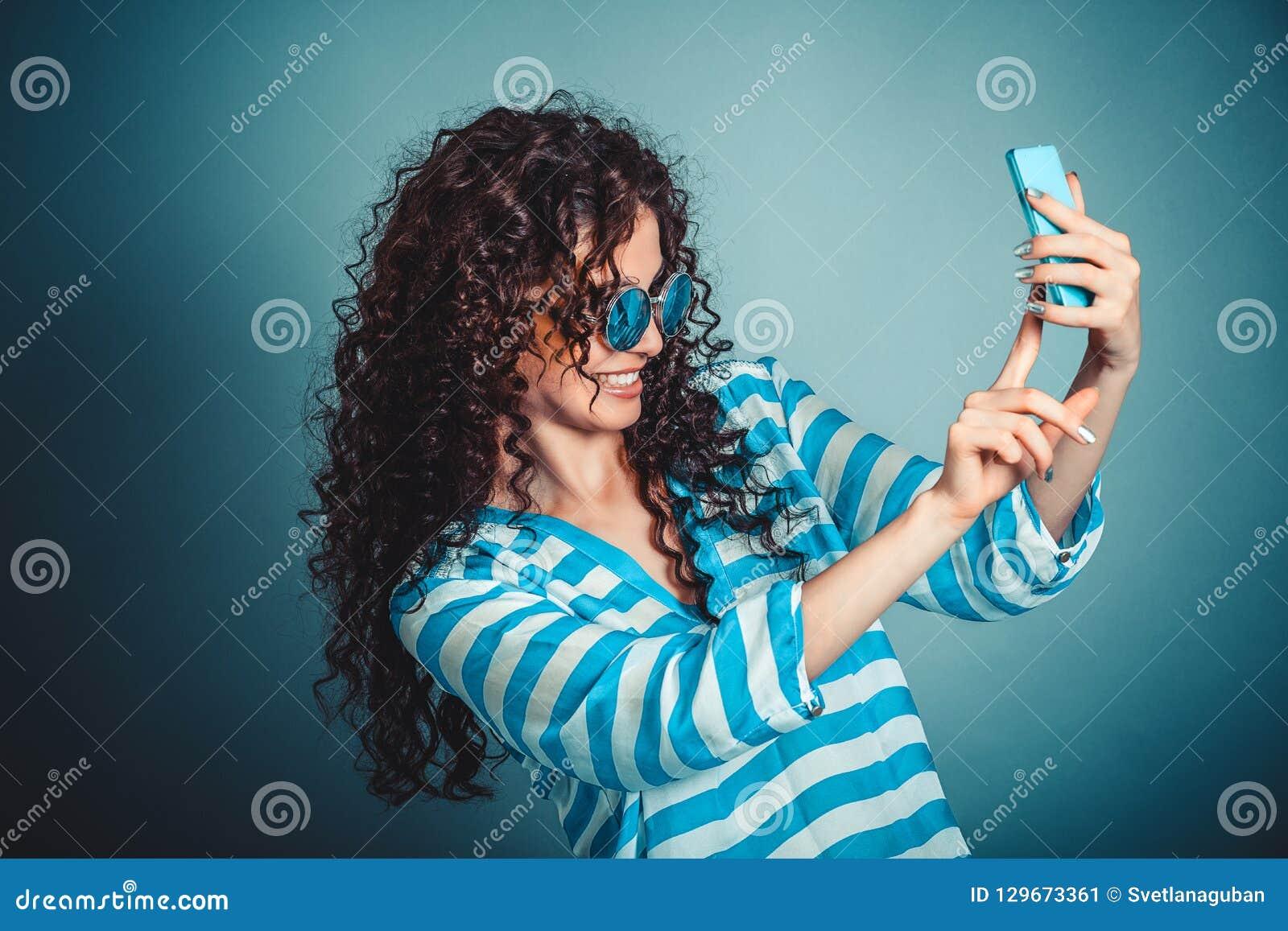 Mulher que faz o selfie com o smartphone isloated no fundo azul