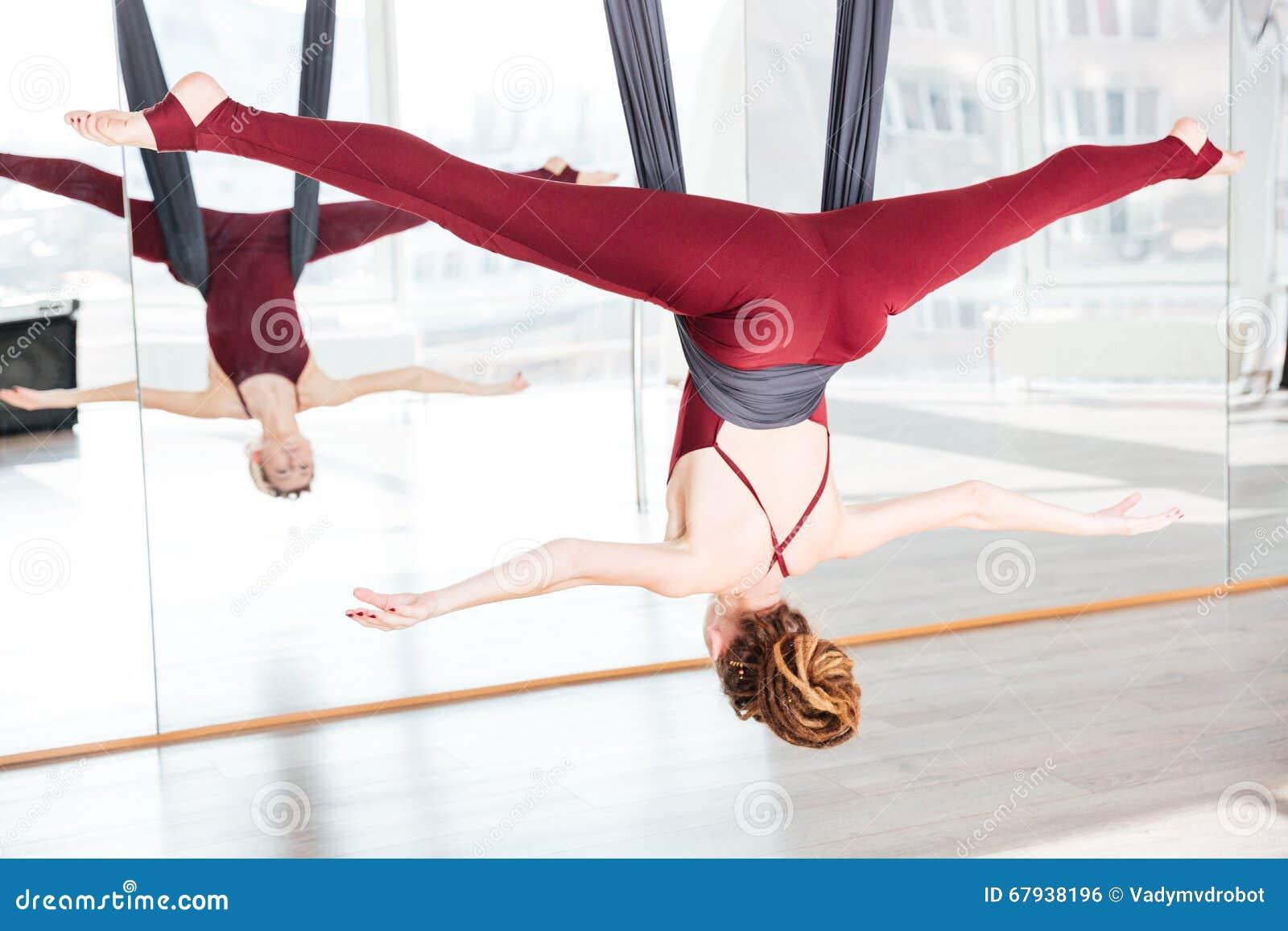 Mulher que faz a pose da ioga antigravitante usando a rede