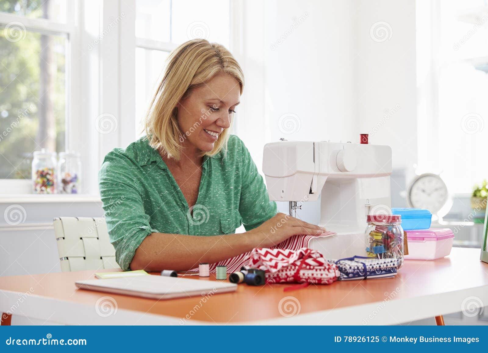 Mulher que faz a roupa usando a máquina de costura em casa