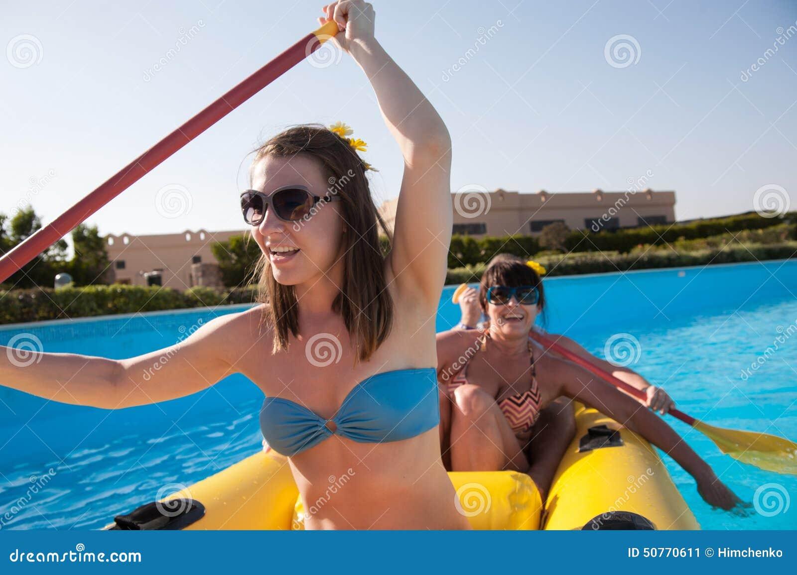Mulher que flutua em um barco inflável