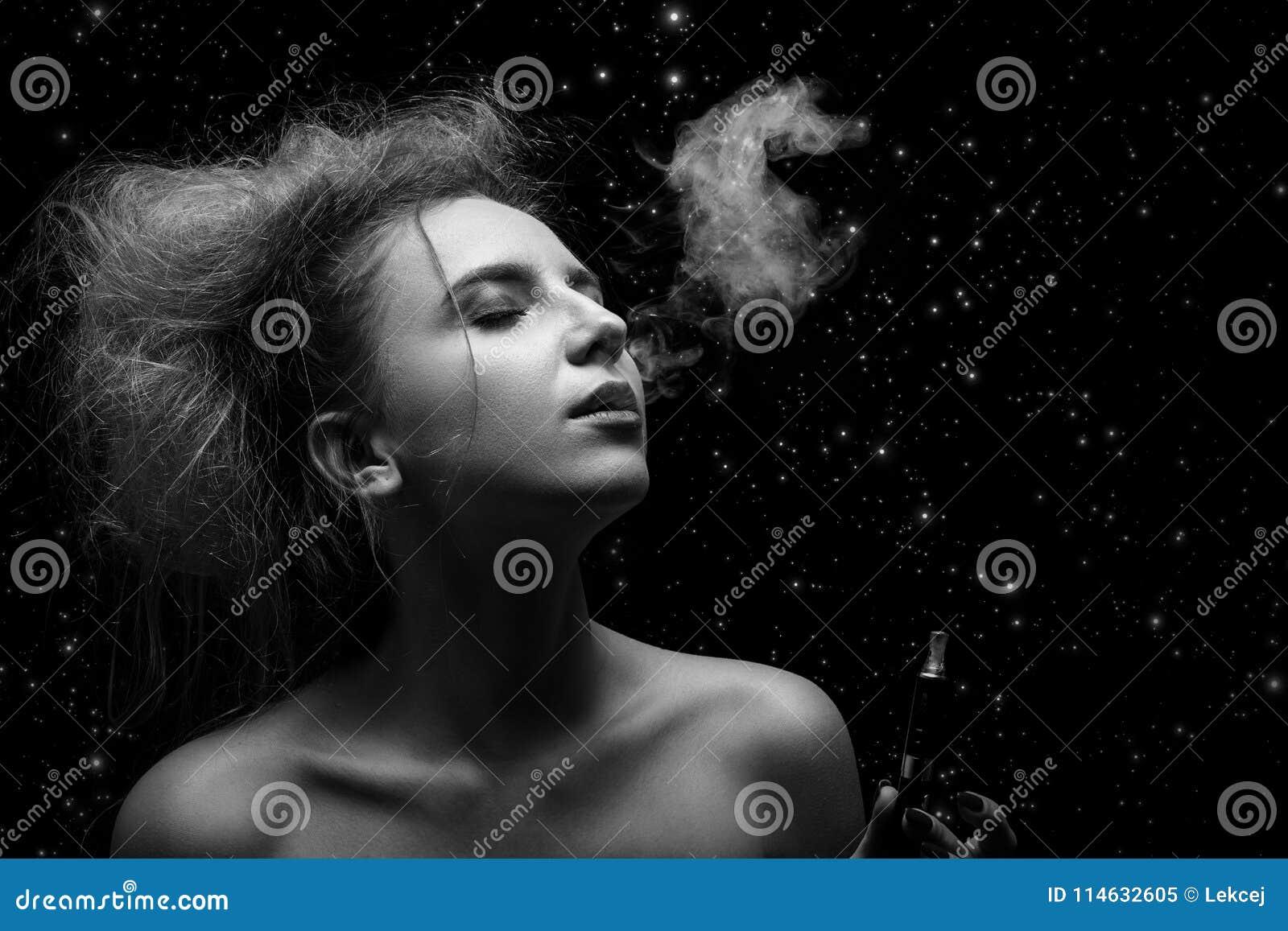 Mulher que fuma o cigarro eletrônico