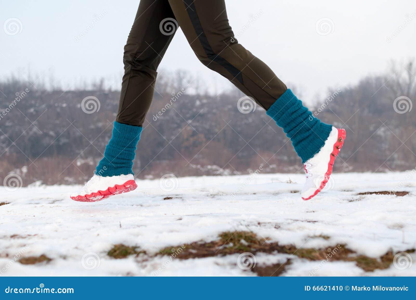 Mulher que funciona na neve