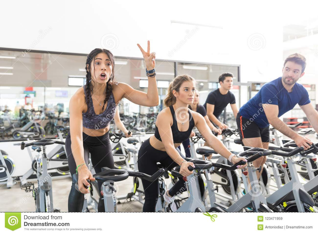 Mulher que gesticula a bicicleta de Victory While Exercising On Spinning no Gym