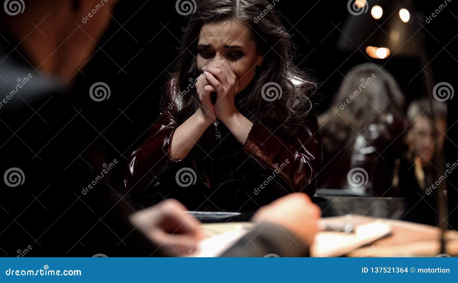 Mulher que grita, foto da exibição do detetive ao parente da vítima após o ato do terrorismo