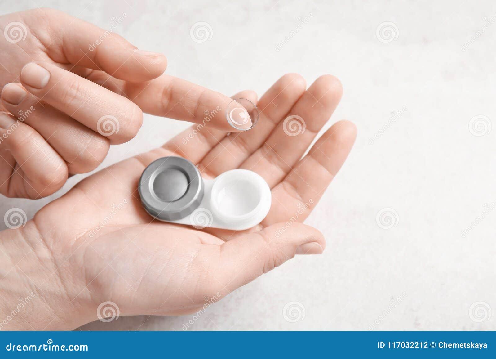 Mulher que guarda a lente de contato e o cas