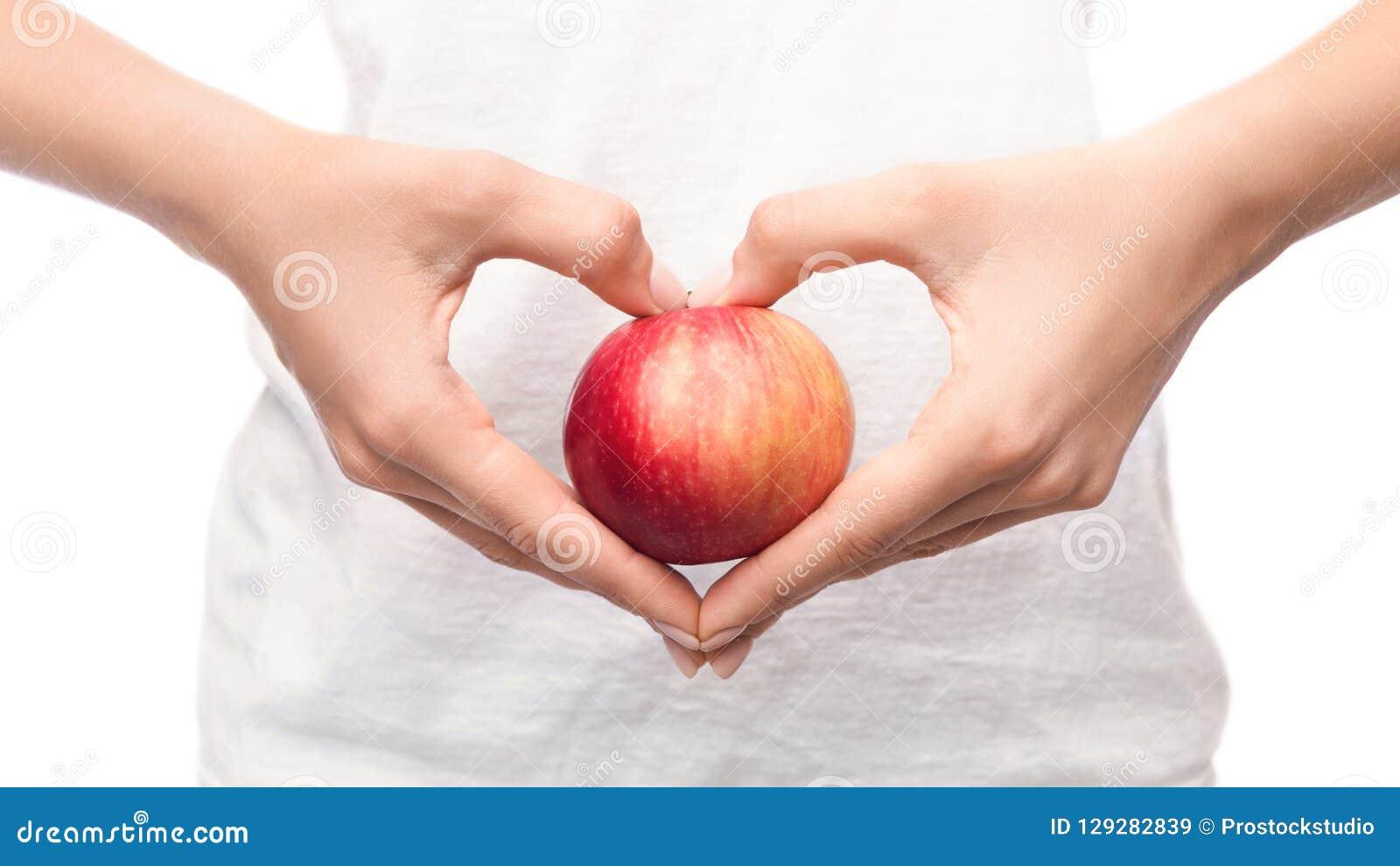 Mulher que guarda a maçã nas mãos dadas forma coração