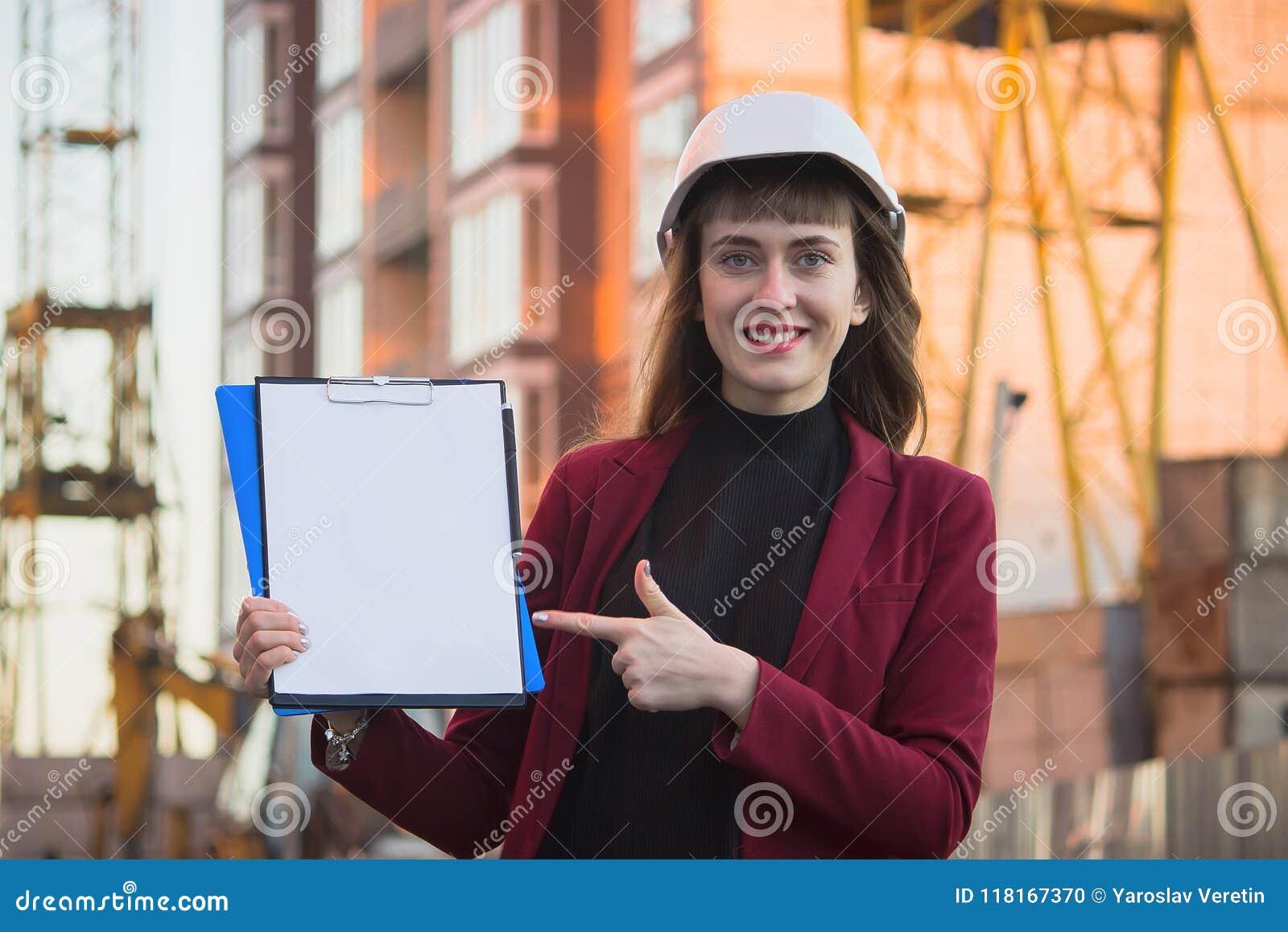 Mulher que guarda modelos, prancheta Arquiteto de sorriso no capacete na construção