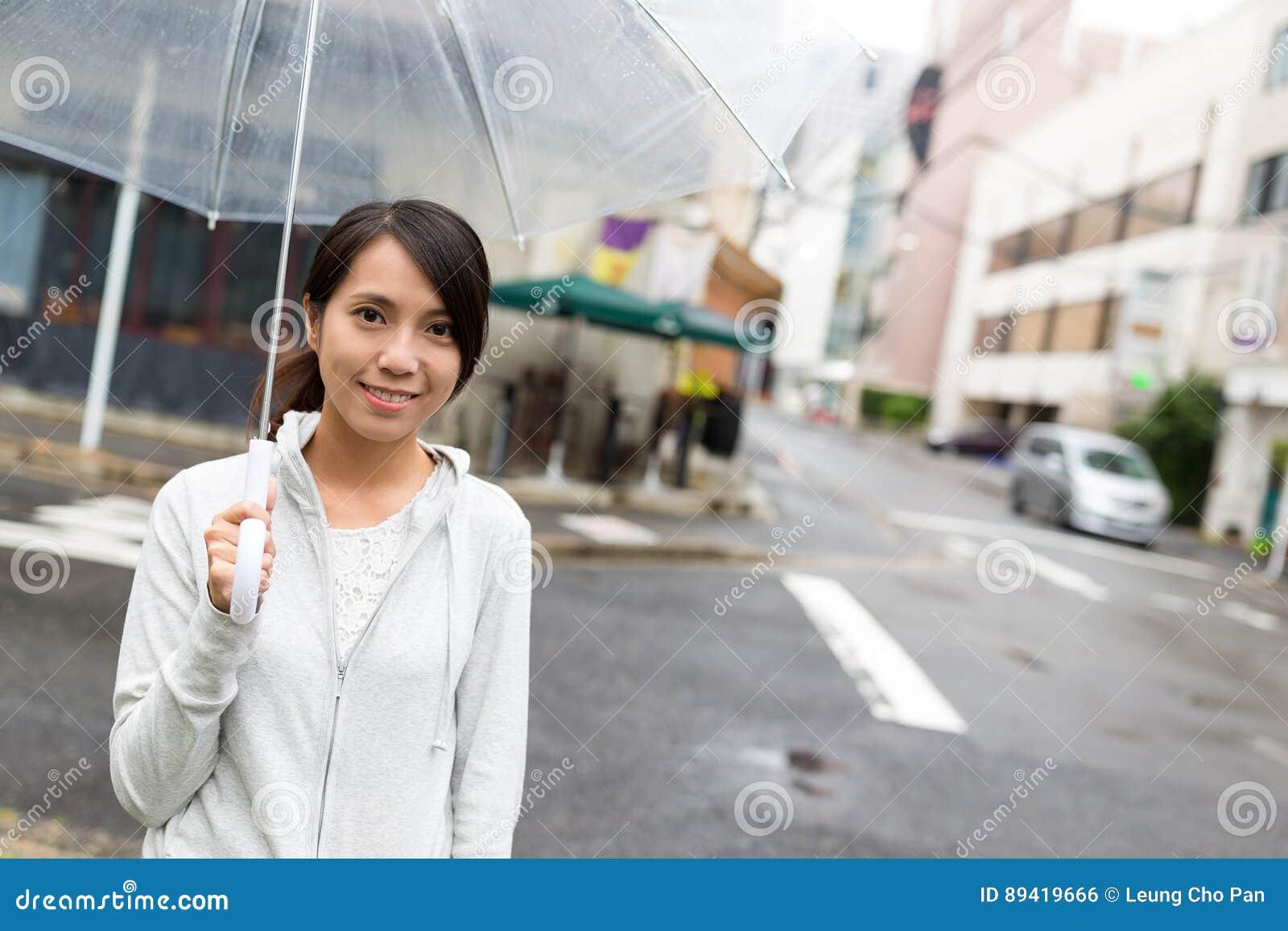 Mulher que guarda o guarda-chuva no dia chuvoso