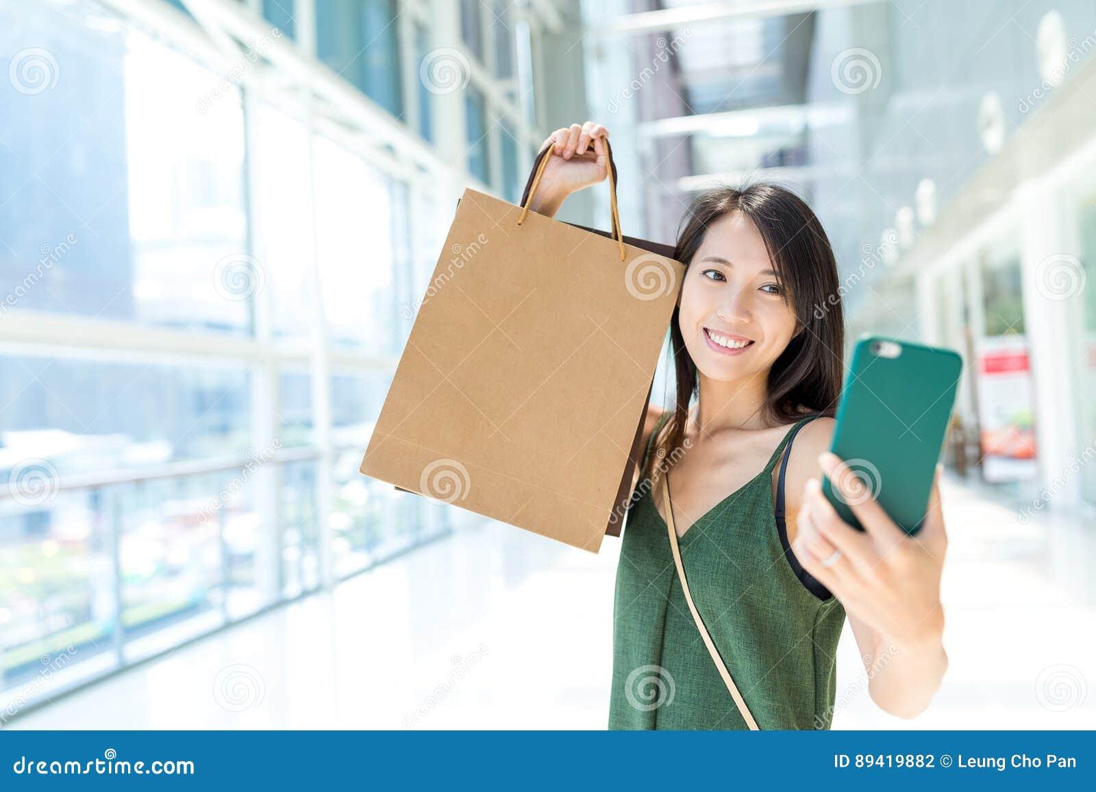Mulher que guarda o saco de compras e que toma o selfie