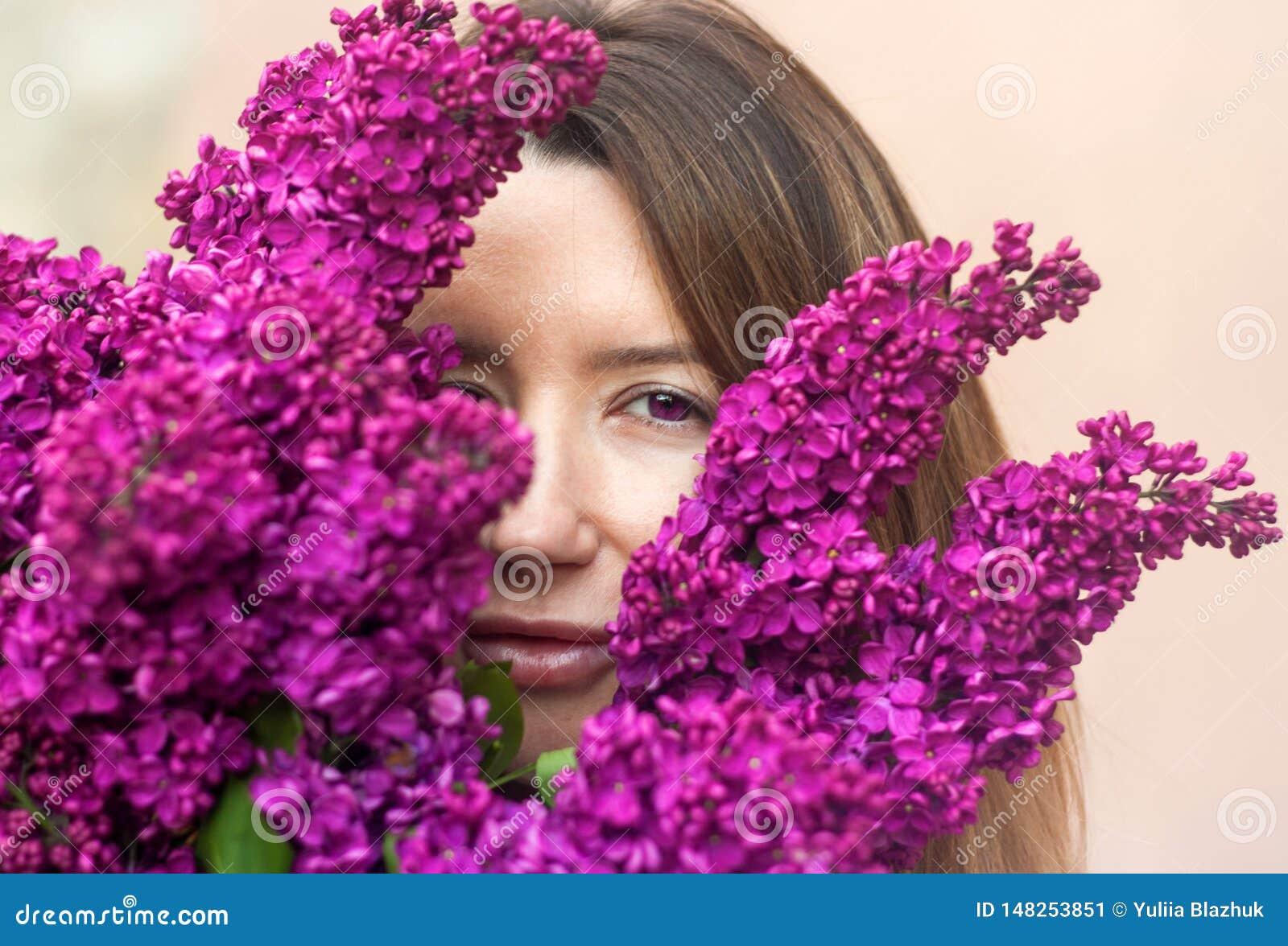 Mulher que guarda um grande ramalhete de flores lilás perto acima