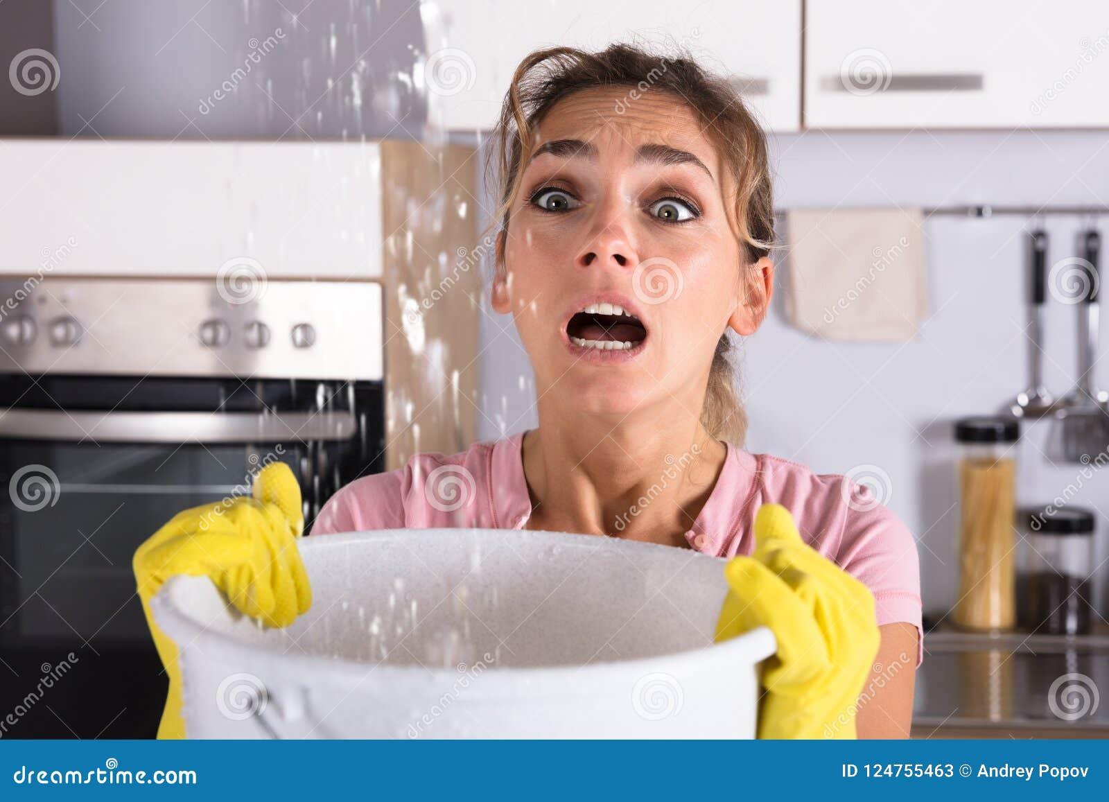 Mulher que guarda uma cubeta quando as gotas de água escaparem do teto
