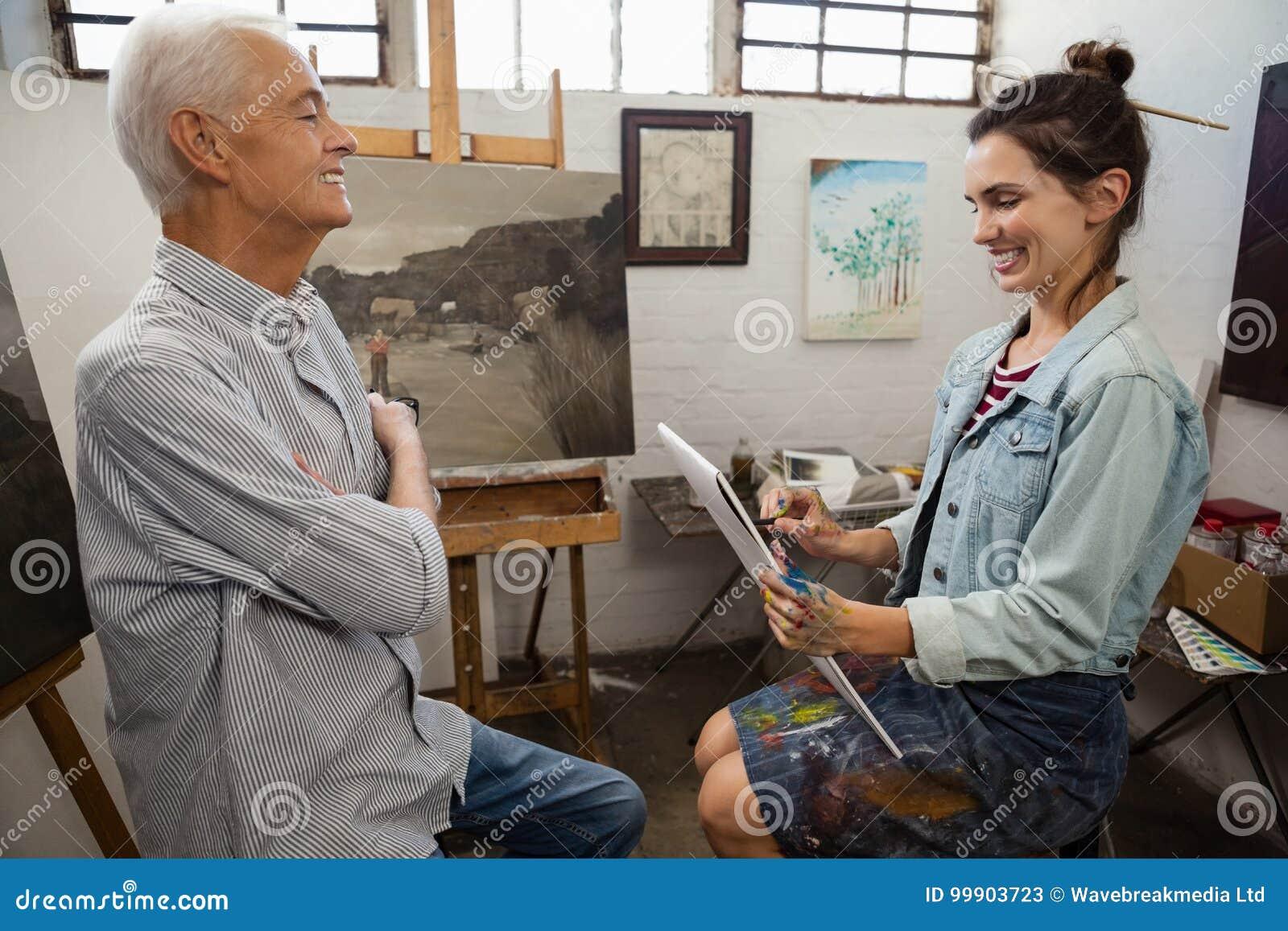 Mulher que interage com o homem superior ao esboçar na lona