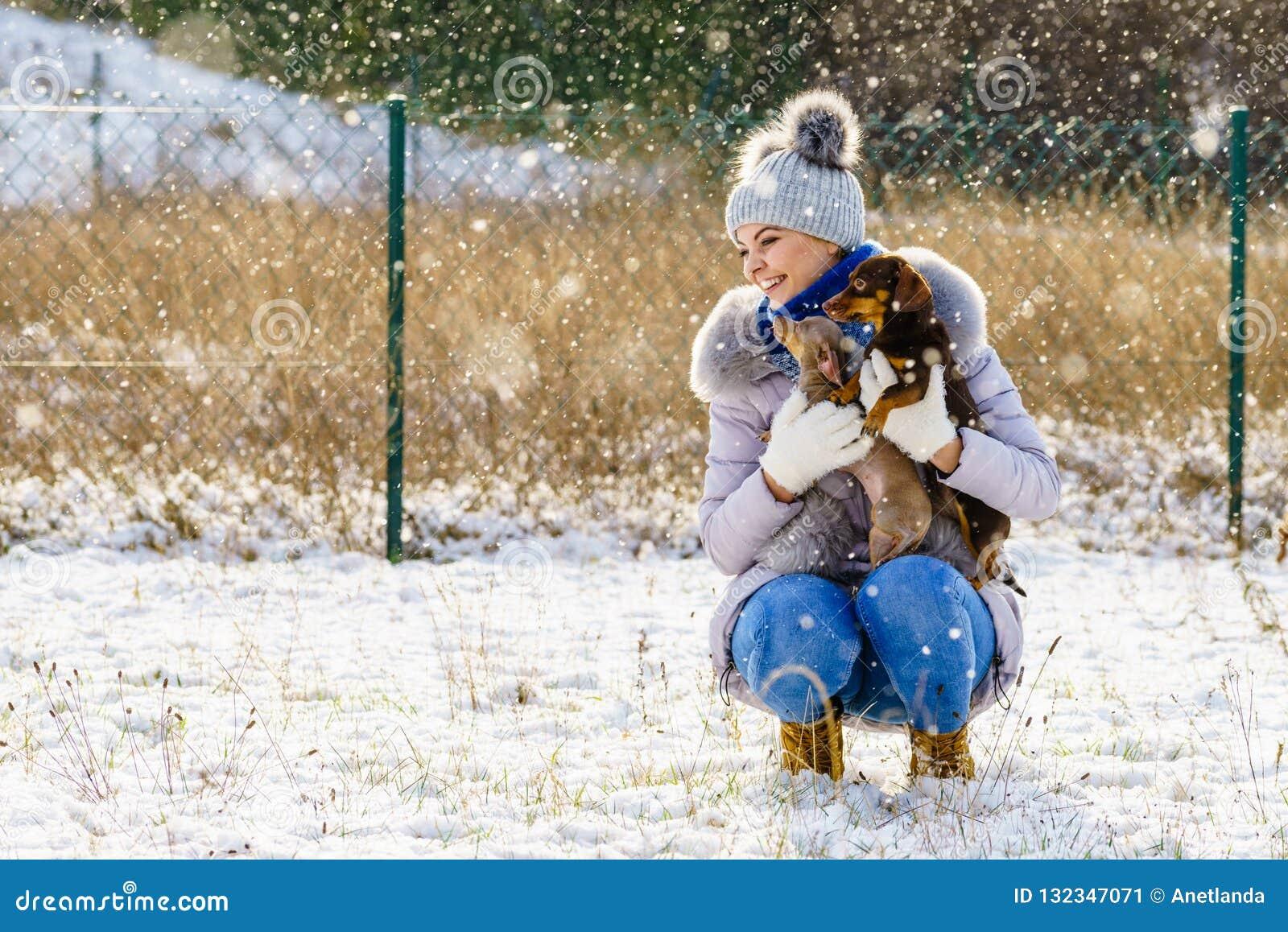 Mulher que joga com os cães durante o inverno