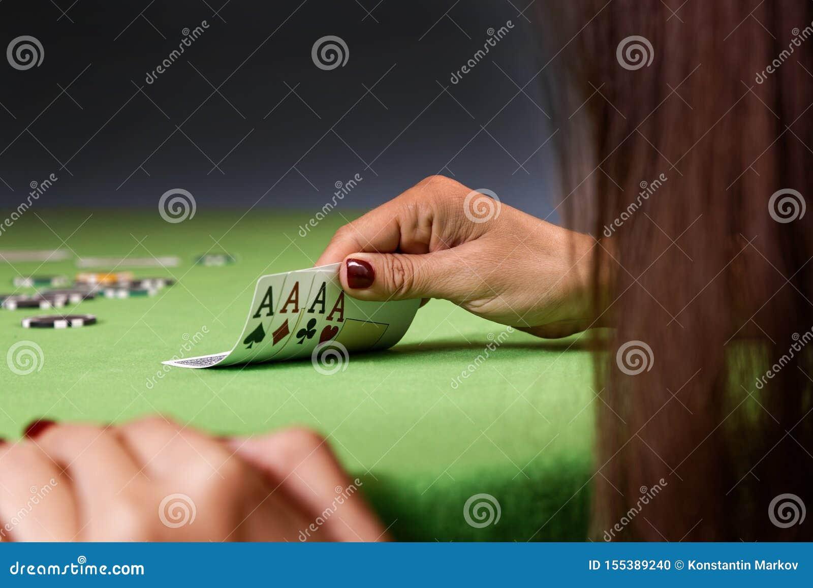 Mulher que joga o jogo de pôquer e que olha cartões Tabela verde, microplaquetas e quatro cartões dos ás à disposição