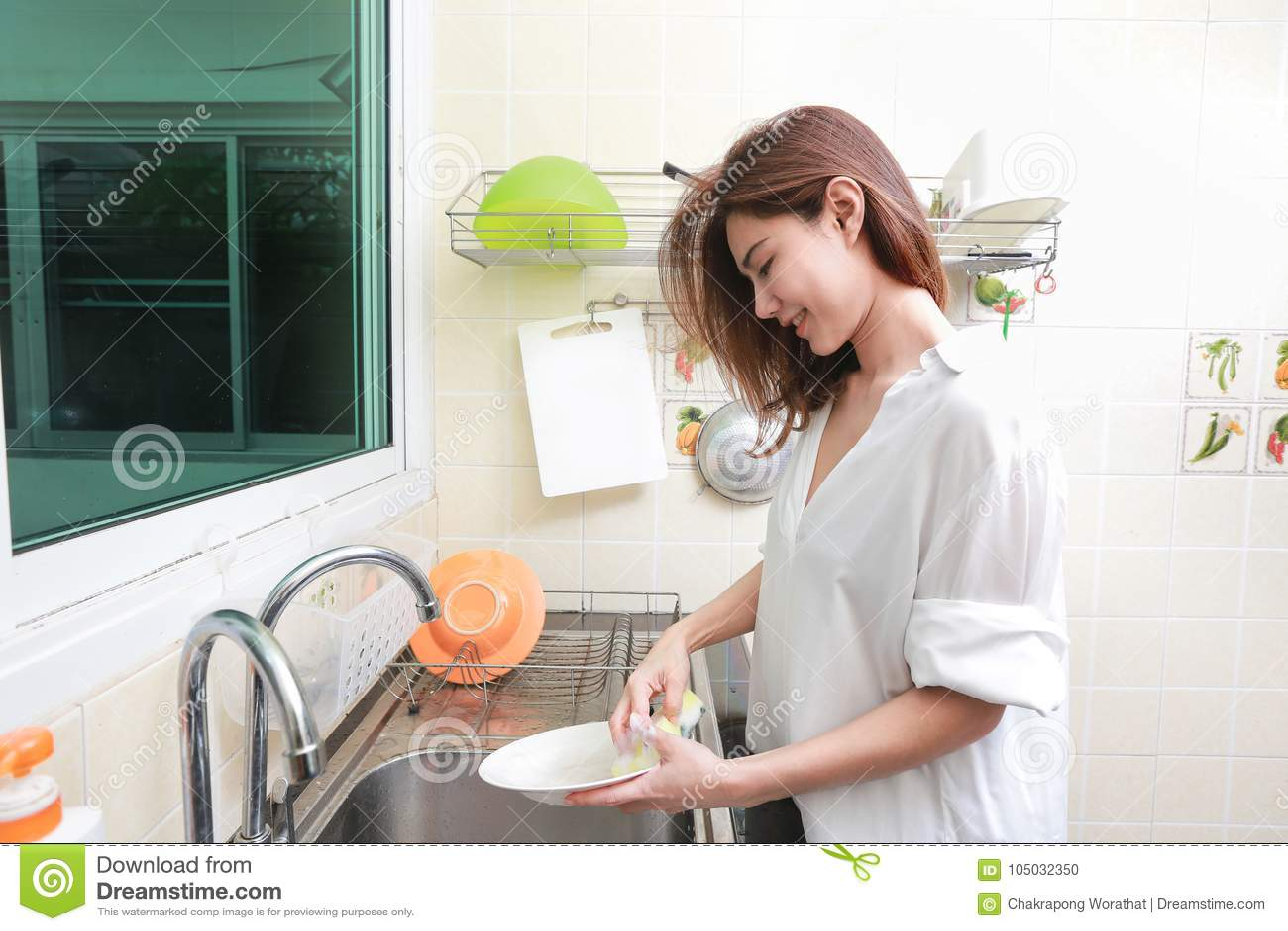 Mulher que lava os pratos na banca da cozinha na casa
