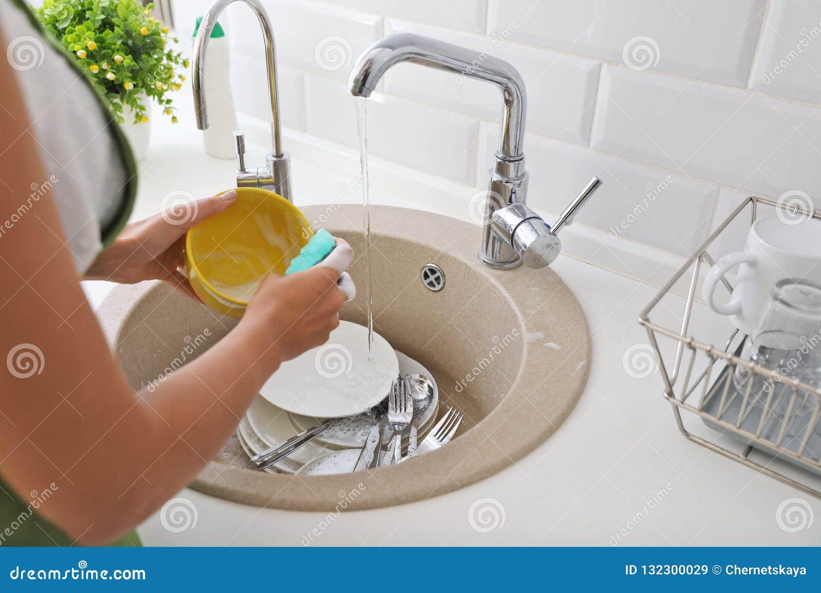 Mulher que lava pratos sujos na banca da cozinha