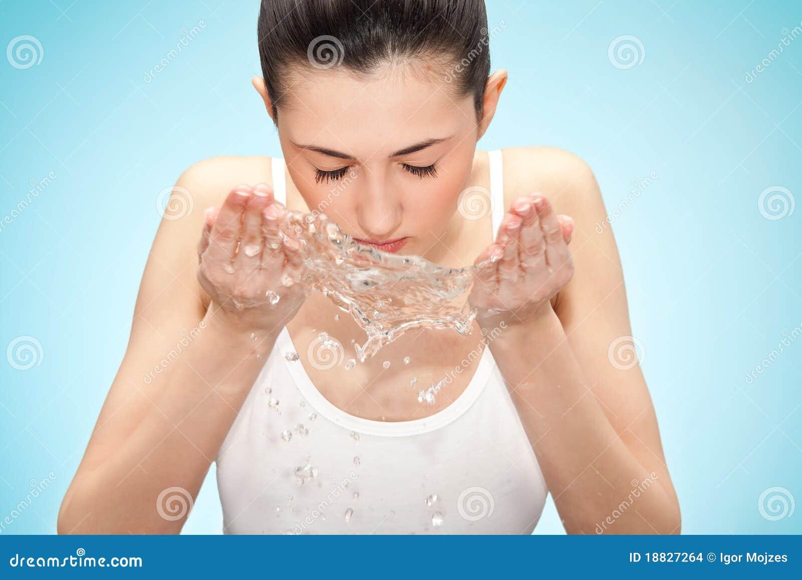 Mulher que lava sua face