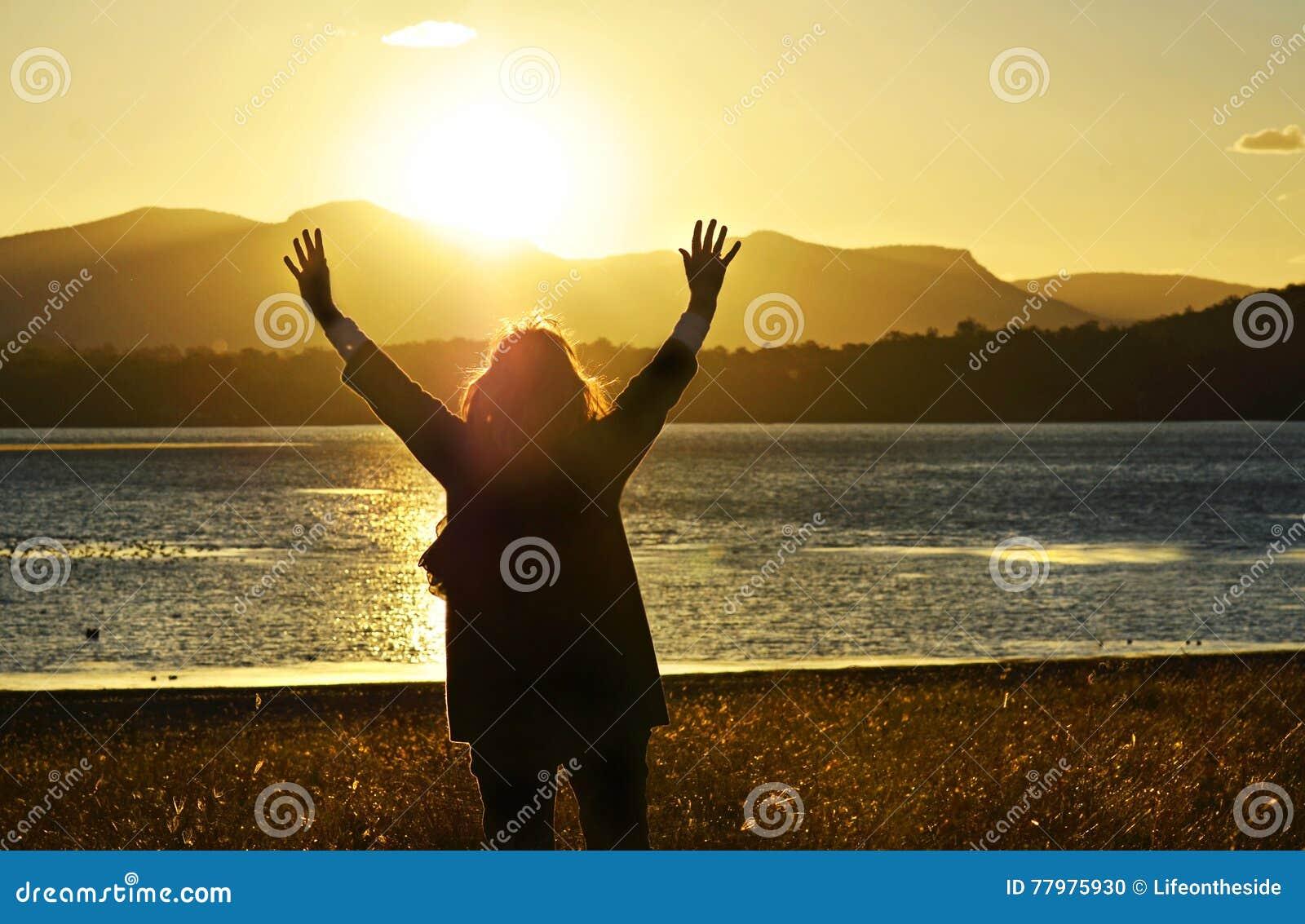 Mulher que levanta as mãos que adoram o elogio rezando o por do sol bonito do deus