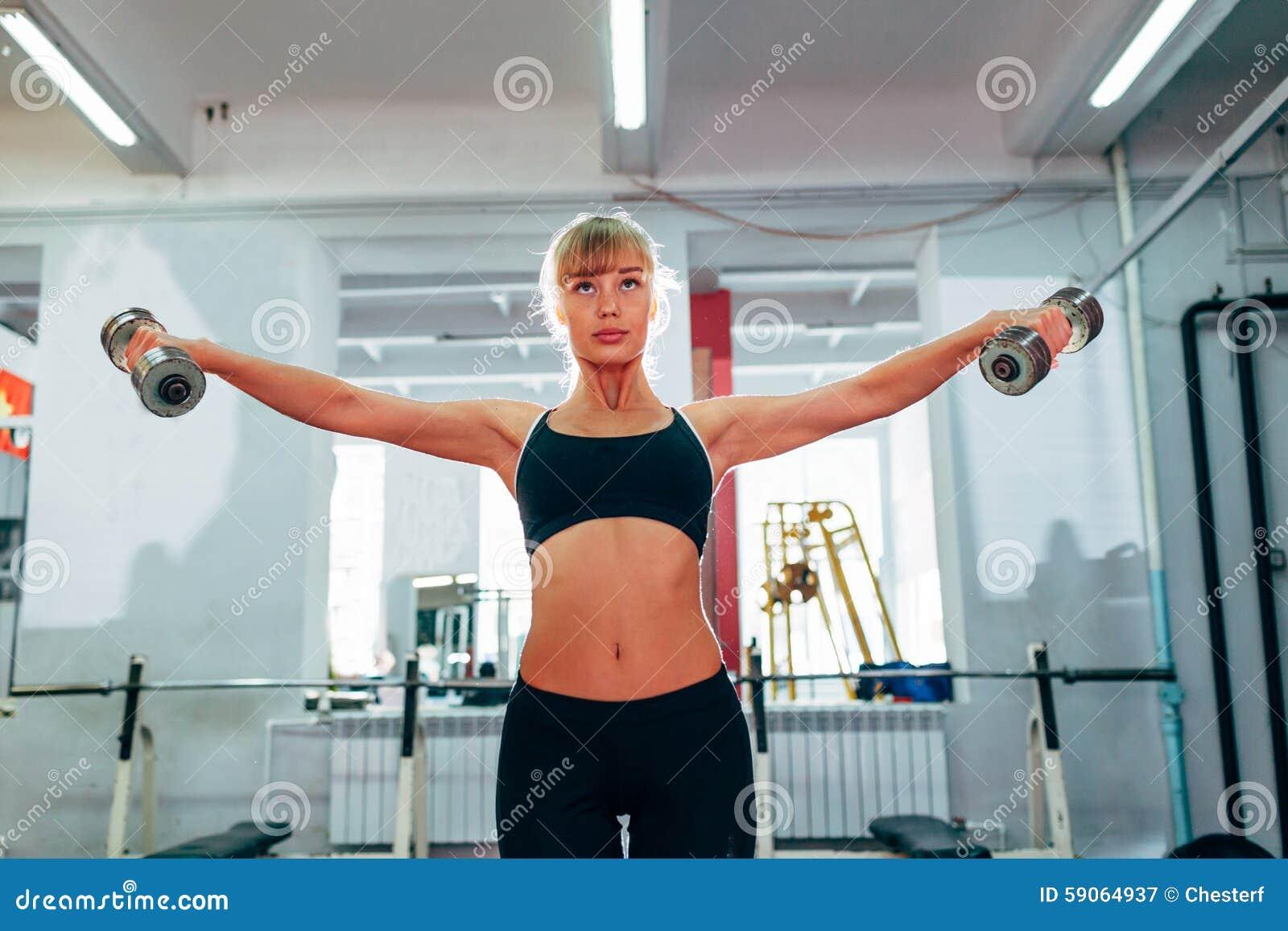 Mulher que levanta pesos no gym