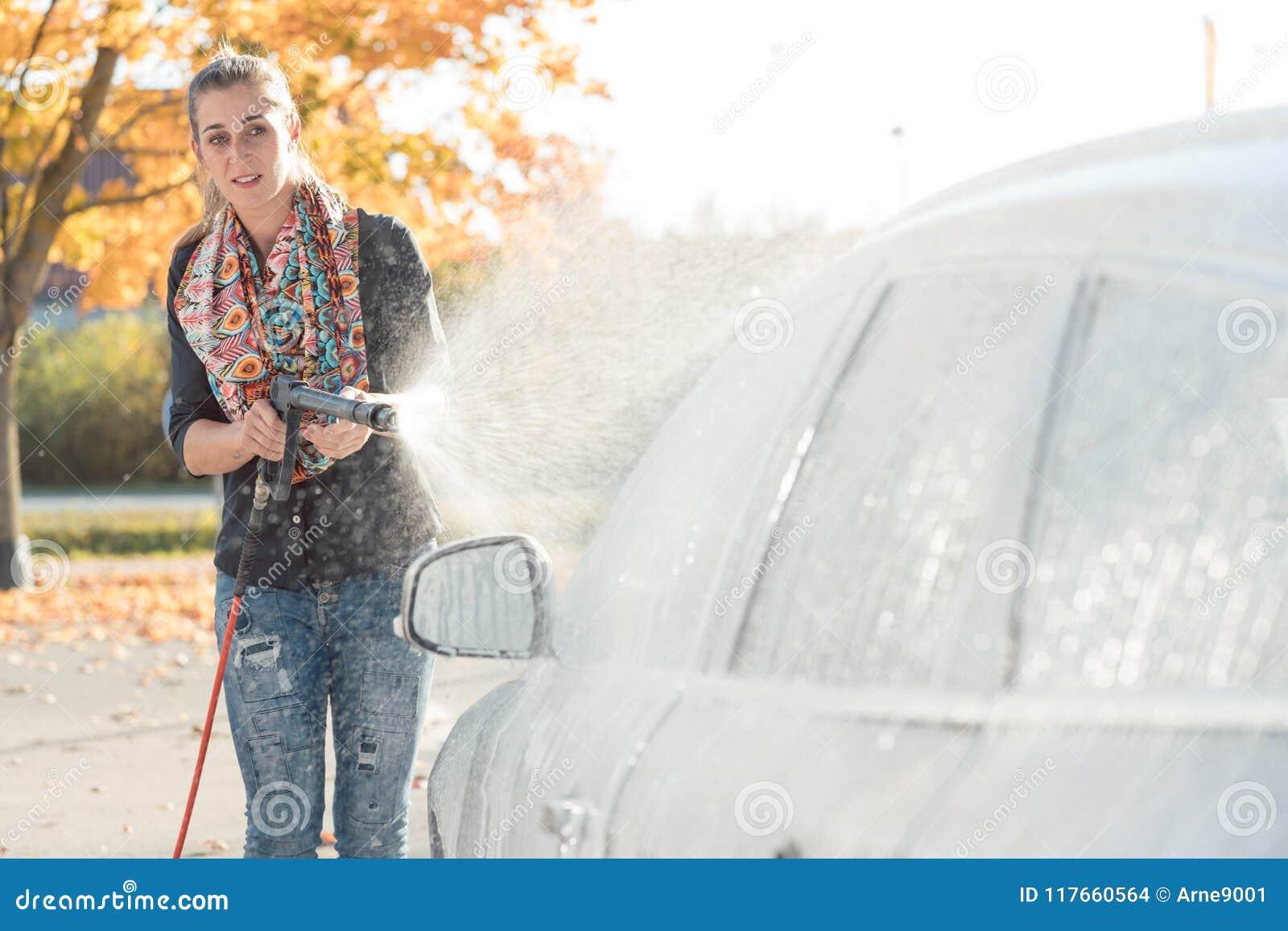 Mulher que limpa seu veículo na lavagem de carros do autosserviço