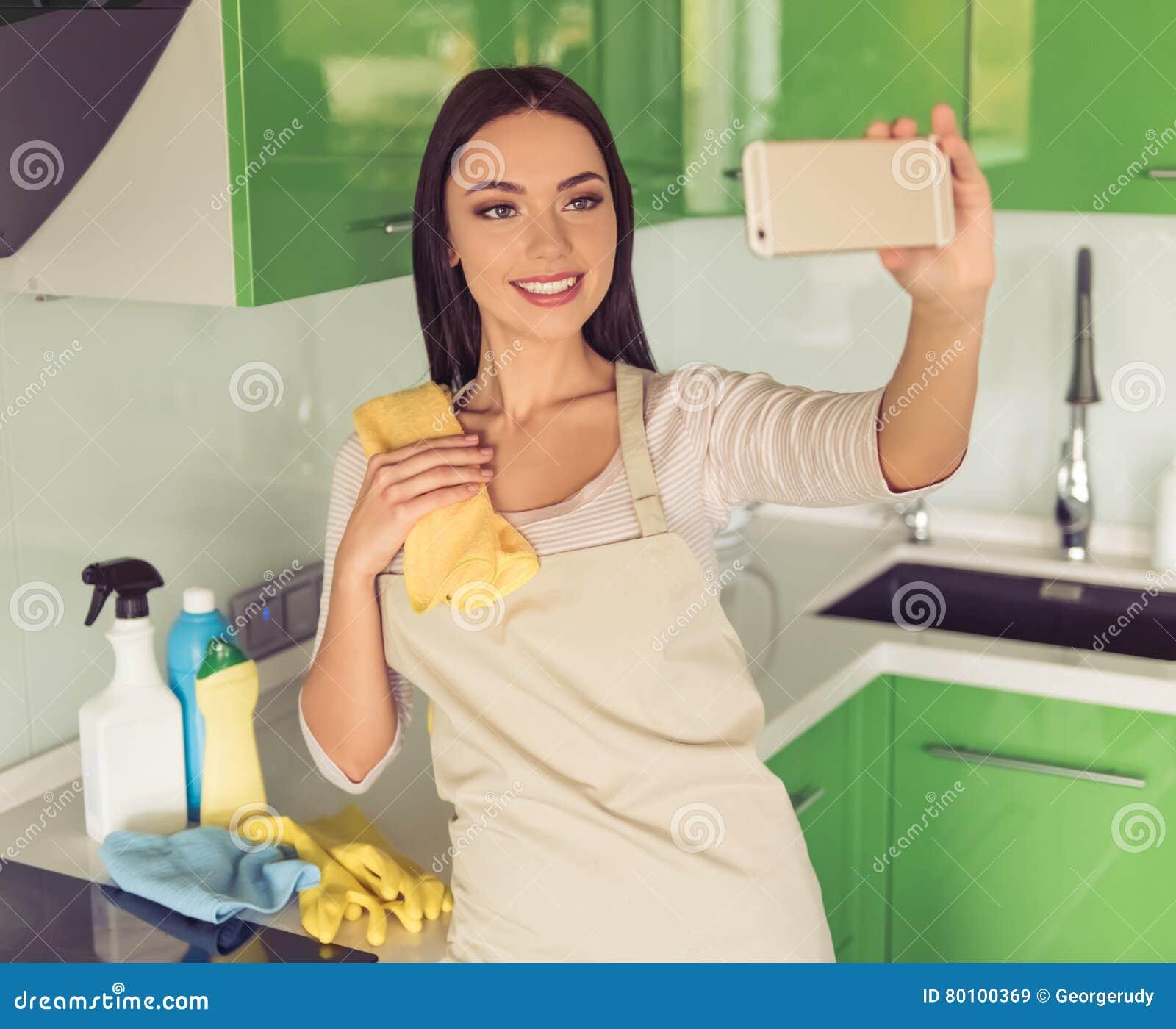 Mulher que limpa sua cozinha