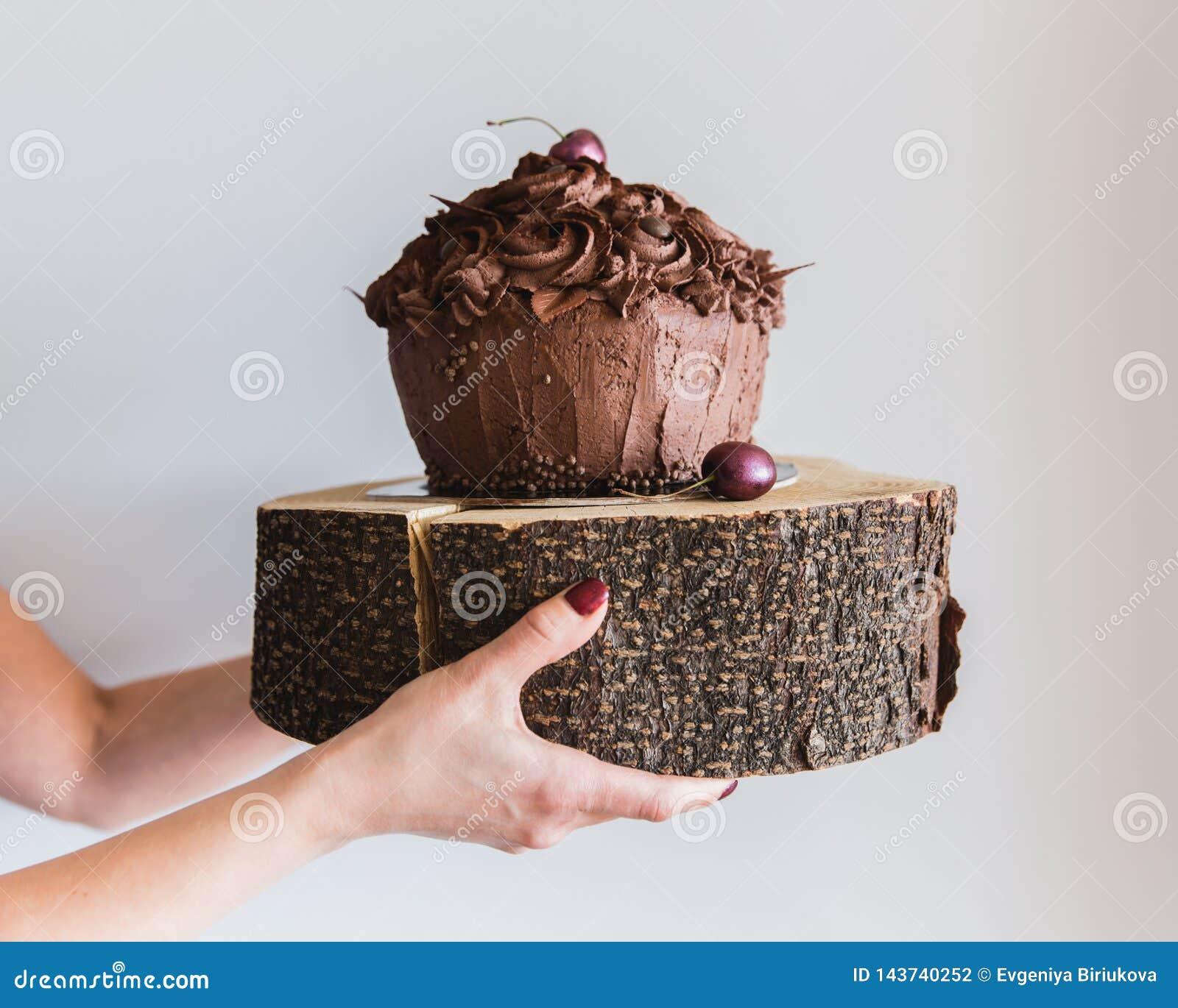 Mulher que mantém um bolo de chocolate em uma placa de madeira, fim Padaria deliciosa e para fornecer a caloria alta