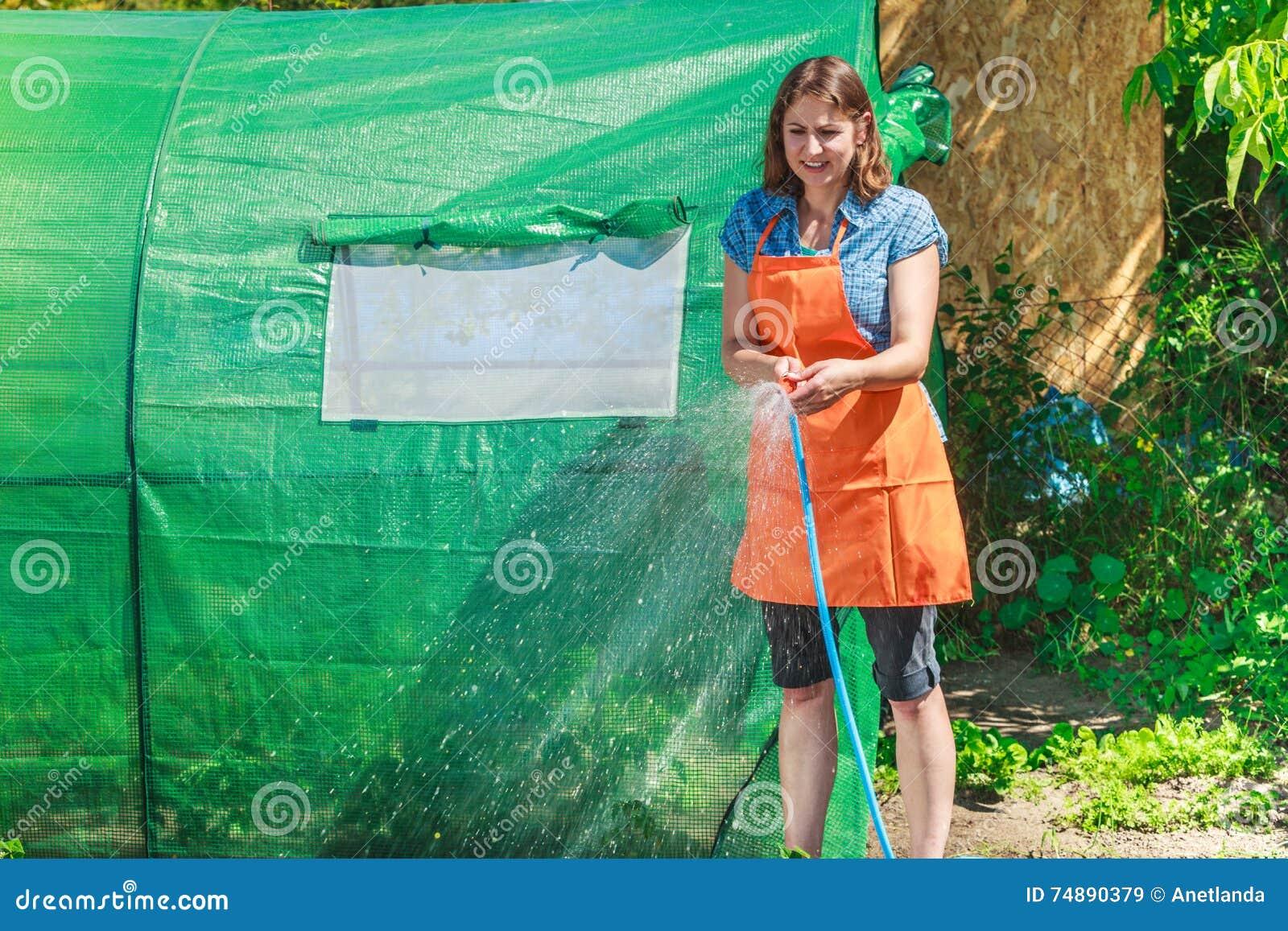 Mulher que molha o jardim com mangueira