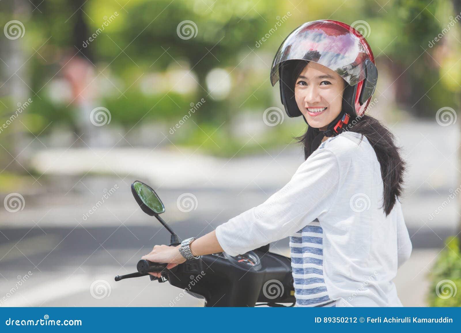 Mulher que monta um motorcyle ou um velomotor