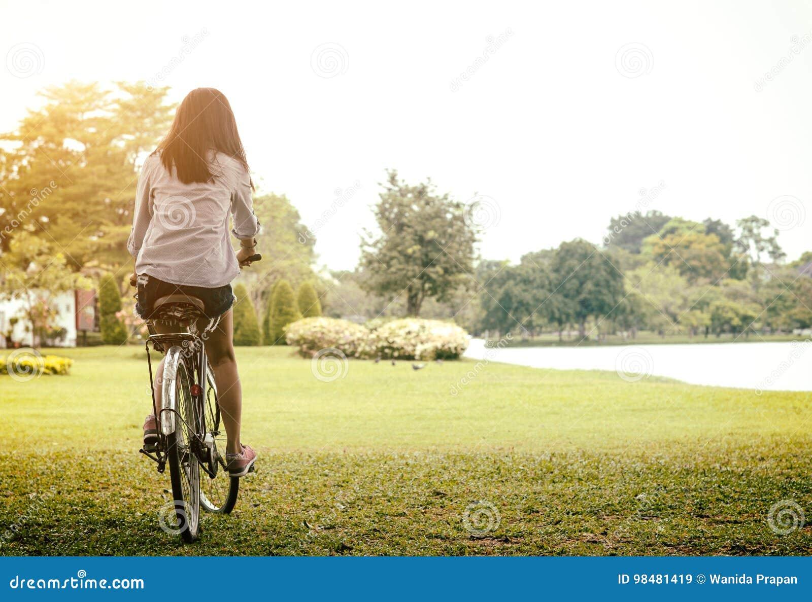 Mulher que monta uma bicicleta em um parque exterior no dia de verão Povos ativos Conceito do estilo de vida