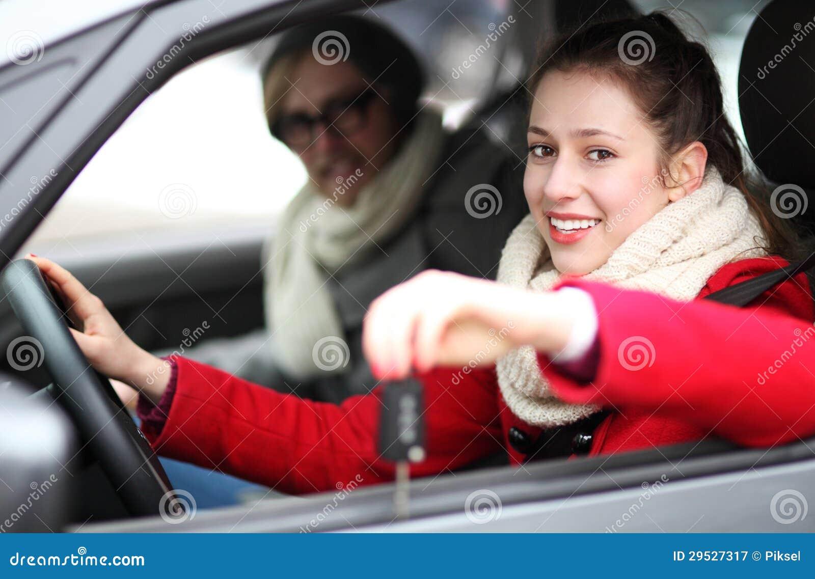Mulher que mostra fora chaves novas do carro