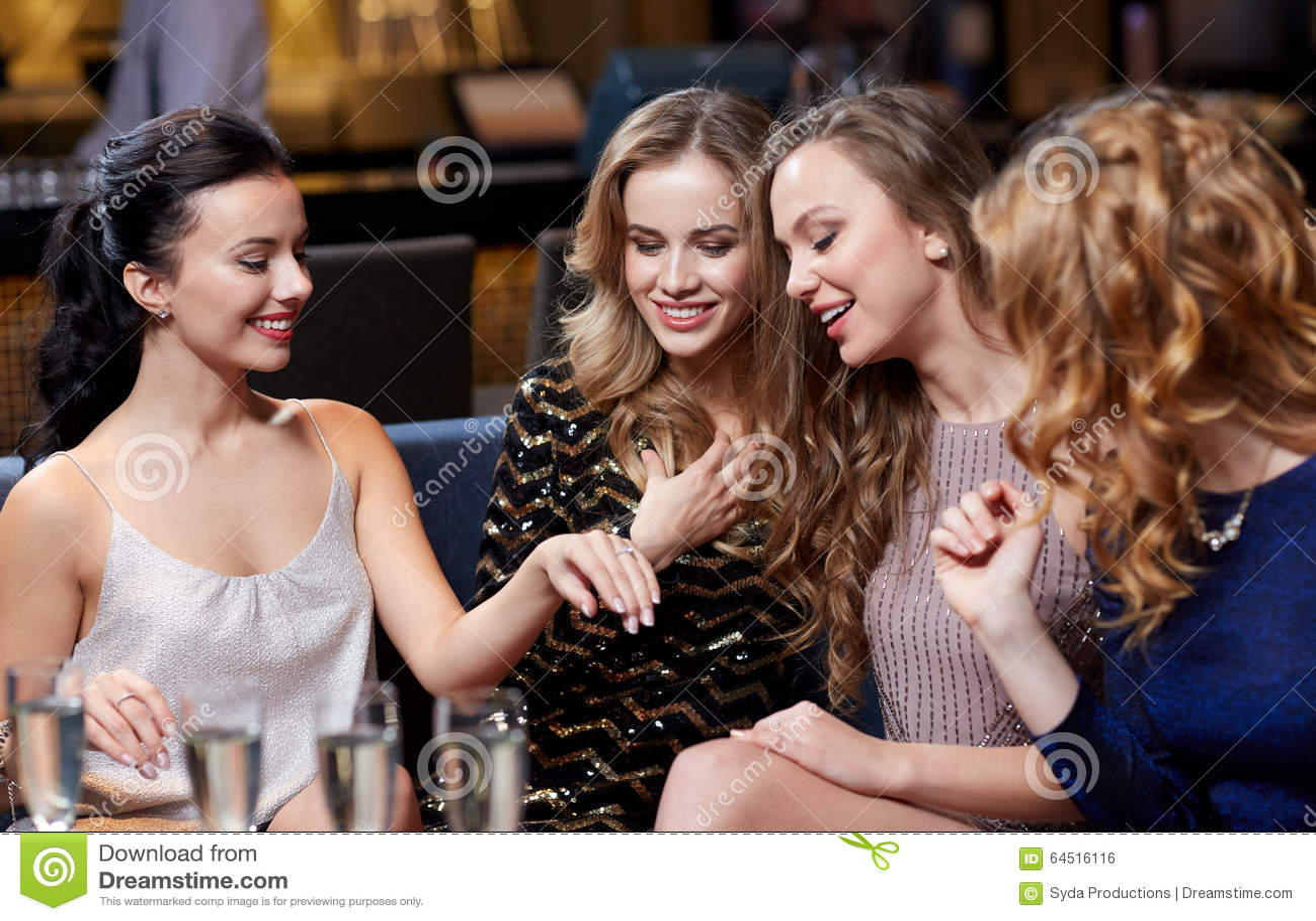Mulher que mostra o anel de noivado a seus amigos