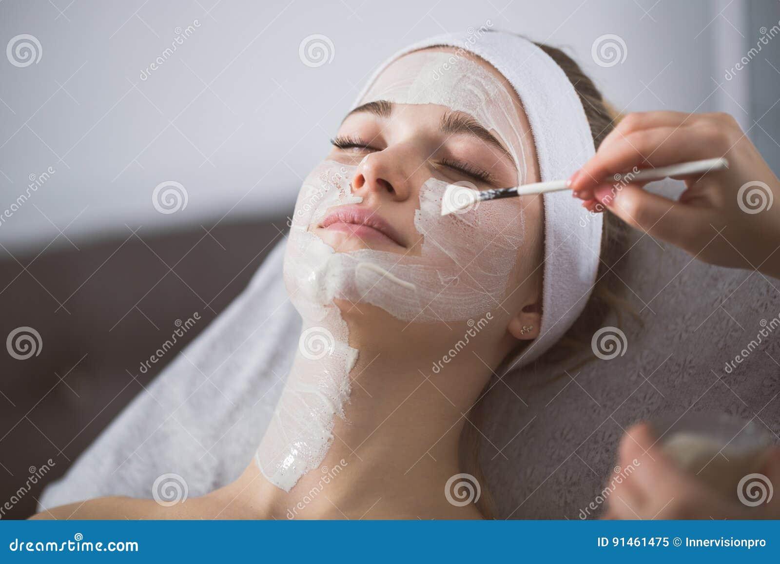 Mulher que obtém a casca enzimático no ` s do esteticista