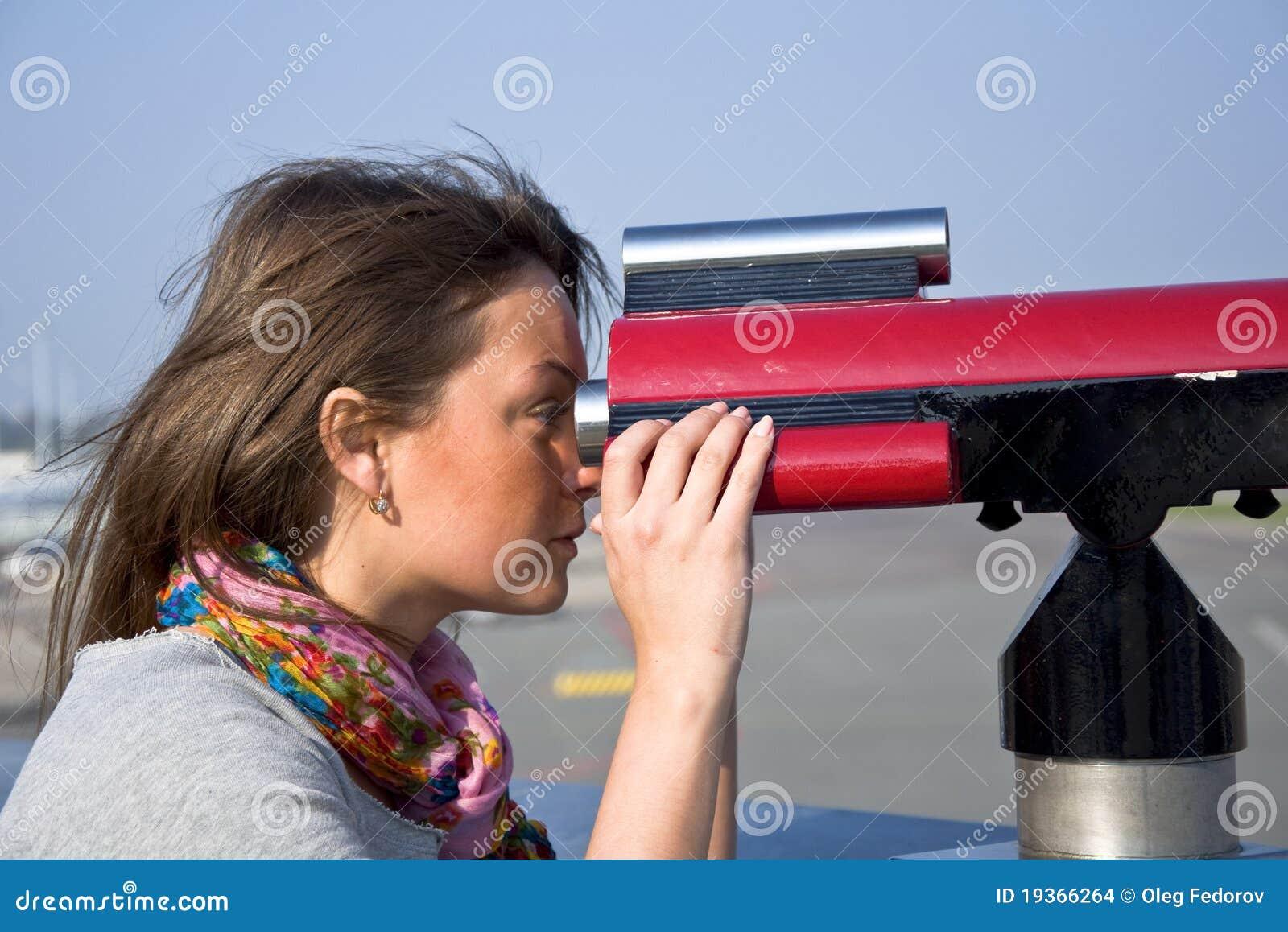 Mulher que olha através de um telescópio
