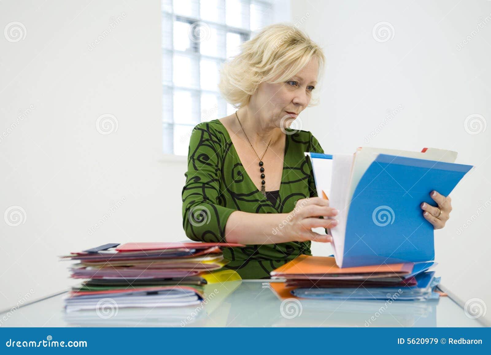 Mulher que olha através dos arquivos