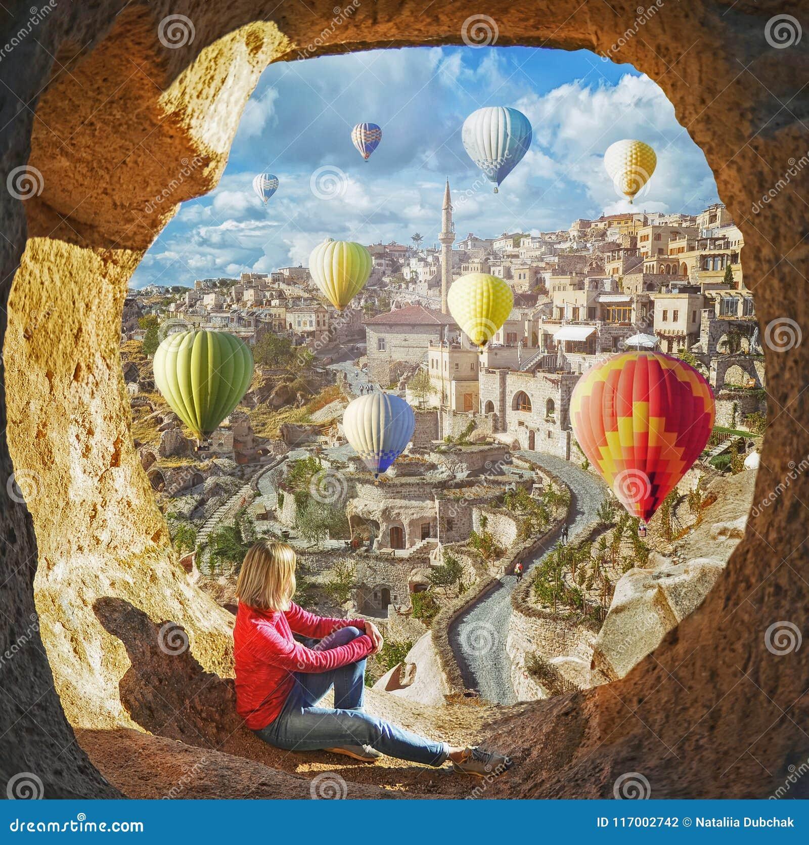 Mulher que olha como os balões de ar quente coloridos que voam sobre o vale em Cappadocia