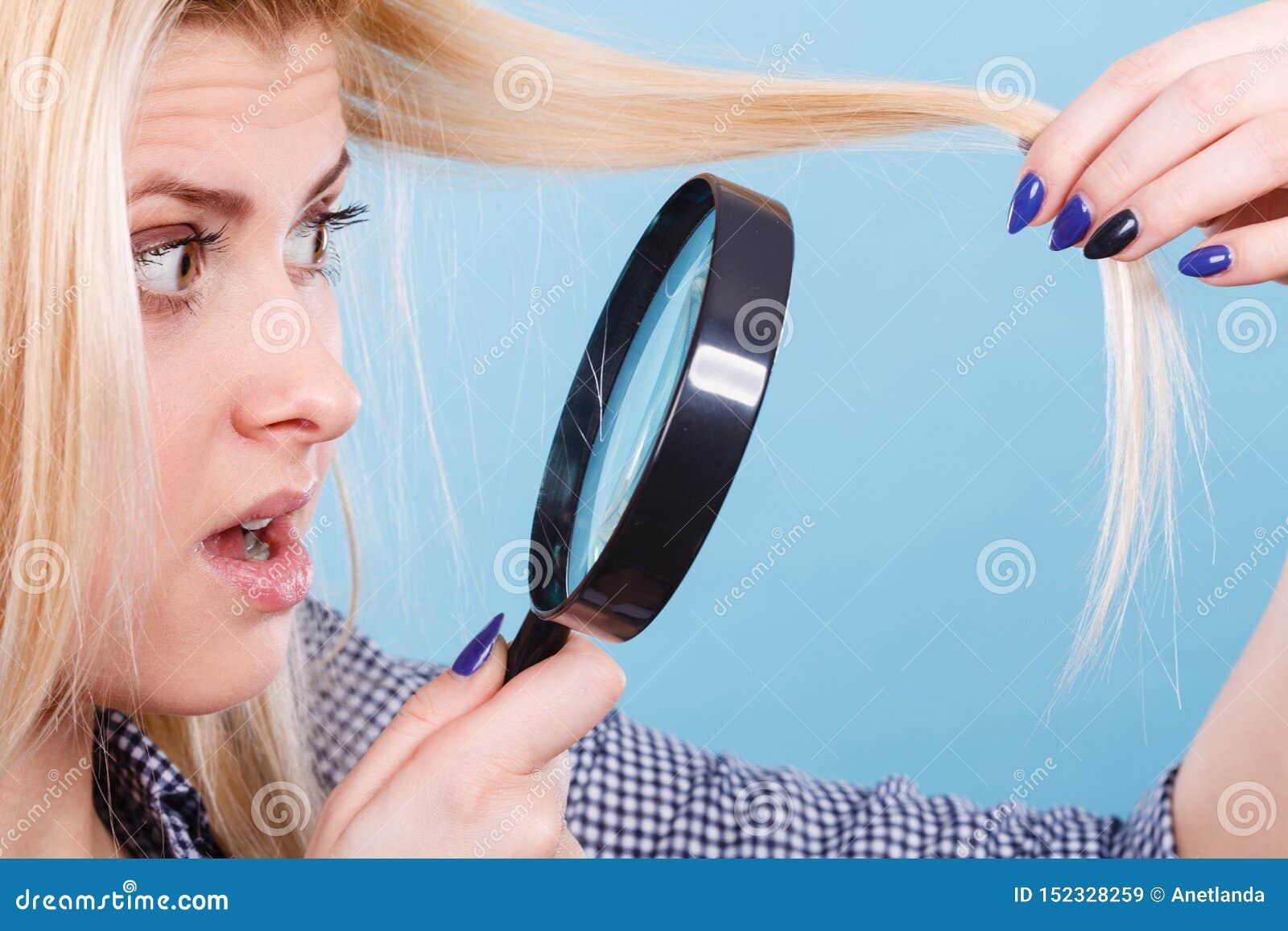 Mulher que olha o cabelo atrav?s da lupa