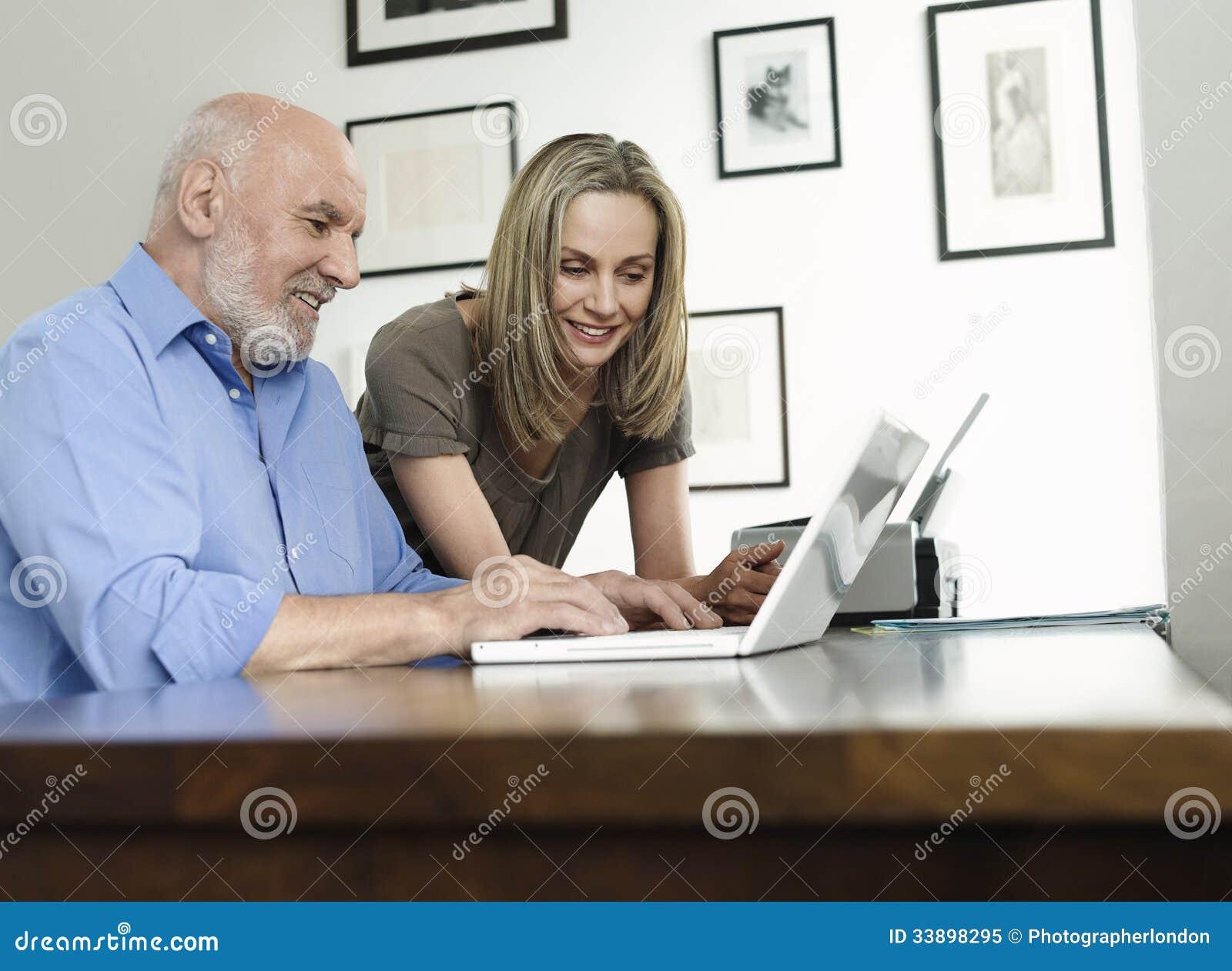 Mulher que olha o portátil maduro do uso do homem em casa