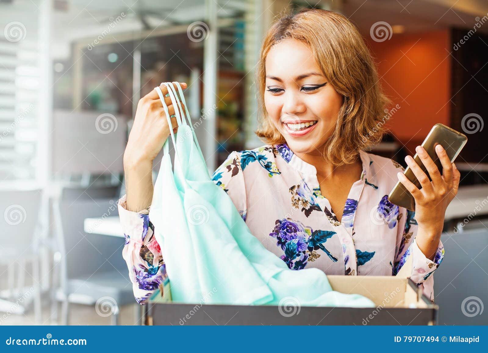 Mulher que olha a roupa que obteve da loja em linha