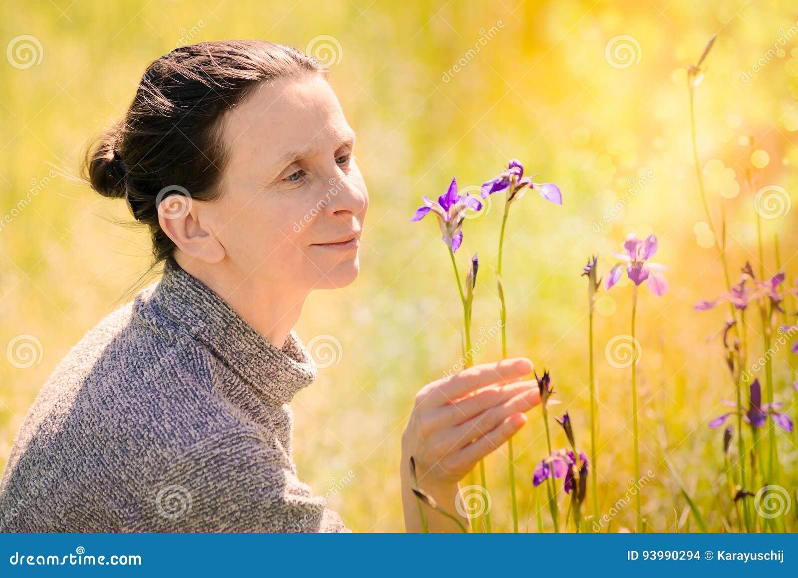 Mulher que olha uma flor selvagem do sibirica da íris
