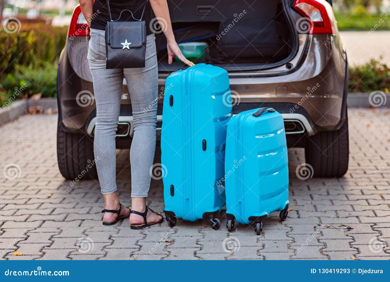 Mulher que põe duas malas de viagem plásticas azuis ao tronco de carro