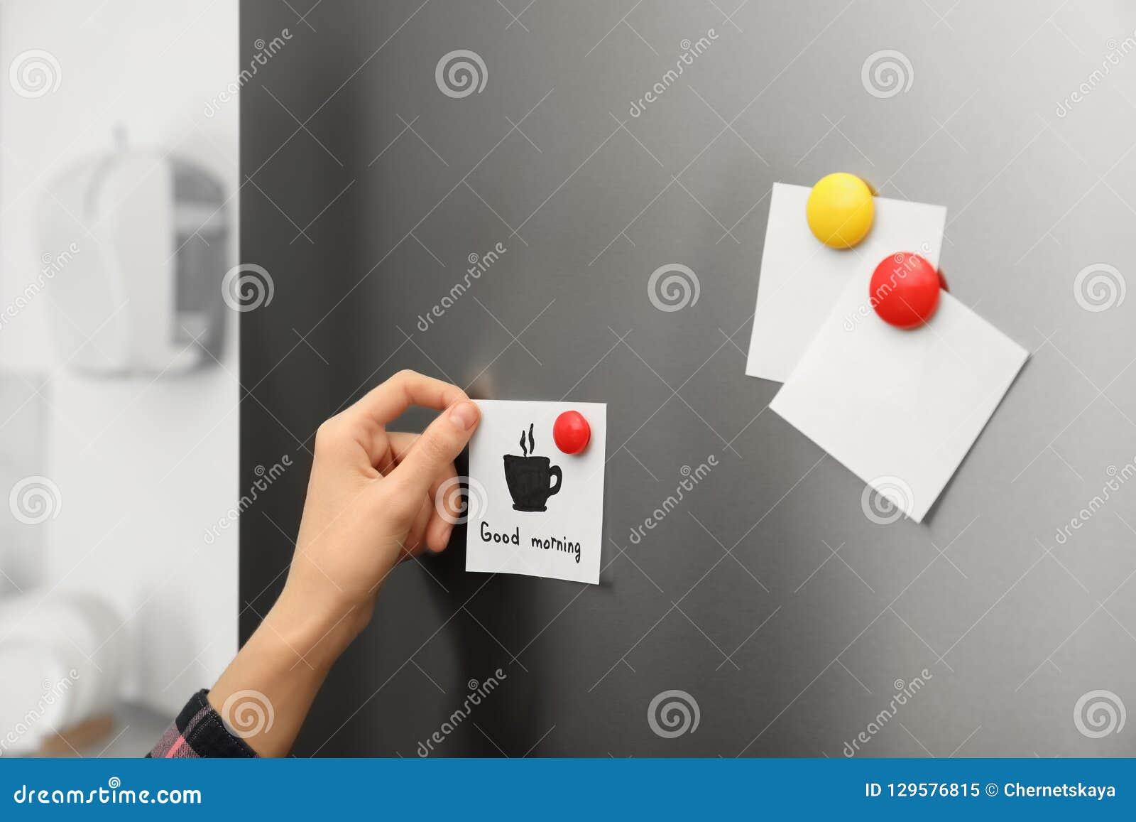 Mulher que põe a folha de papel sobre a porta do refrigerador em casa