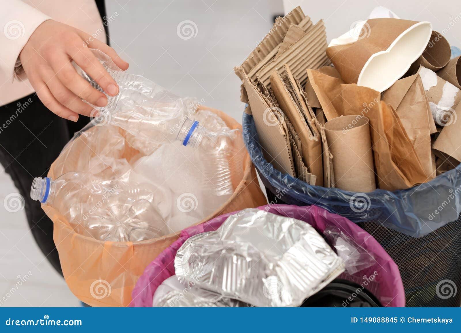 Mulher que põe a garrafa plástica usada no escaninho de lixo Reciclagem de res?duos