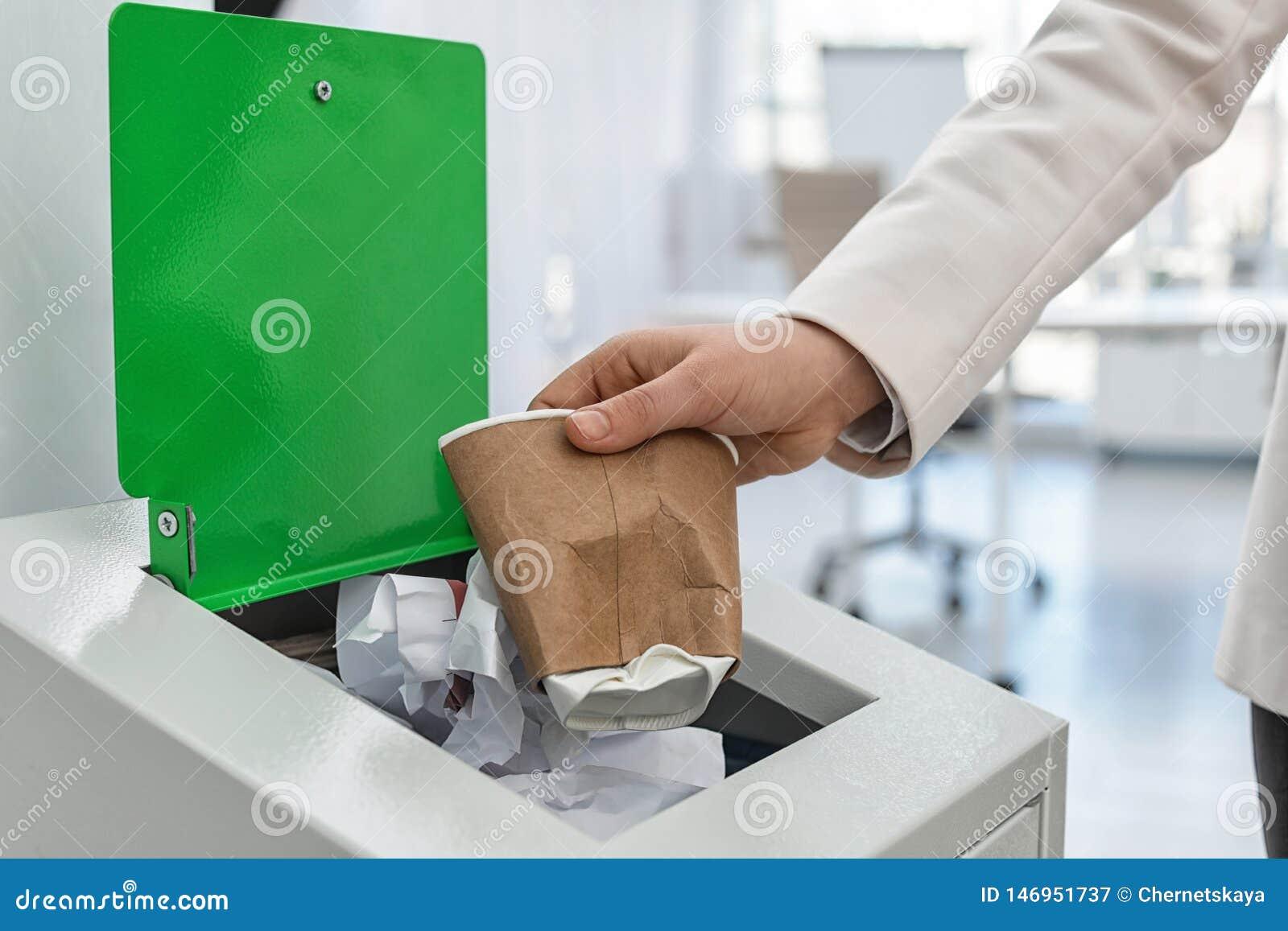 Mulher que p?e o copo de papel usado no escaninho de lixo no escrit?rio moderno Reciclagem de res?duos